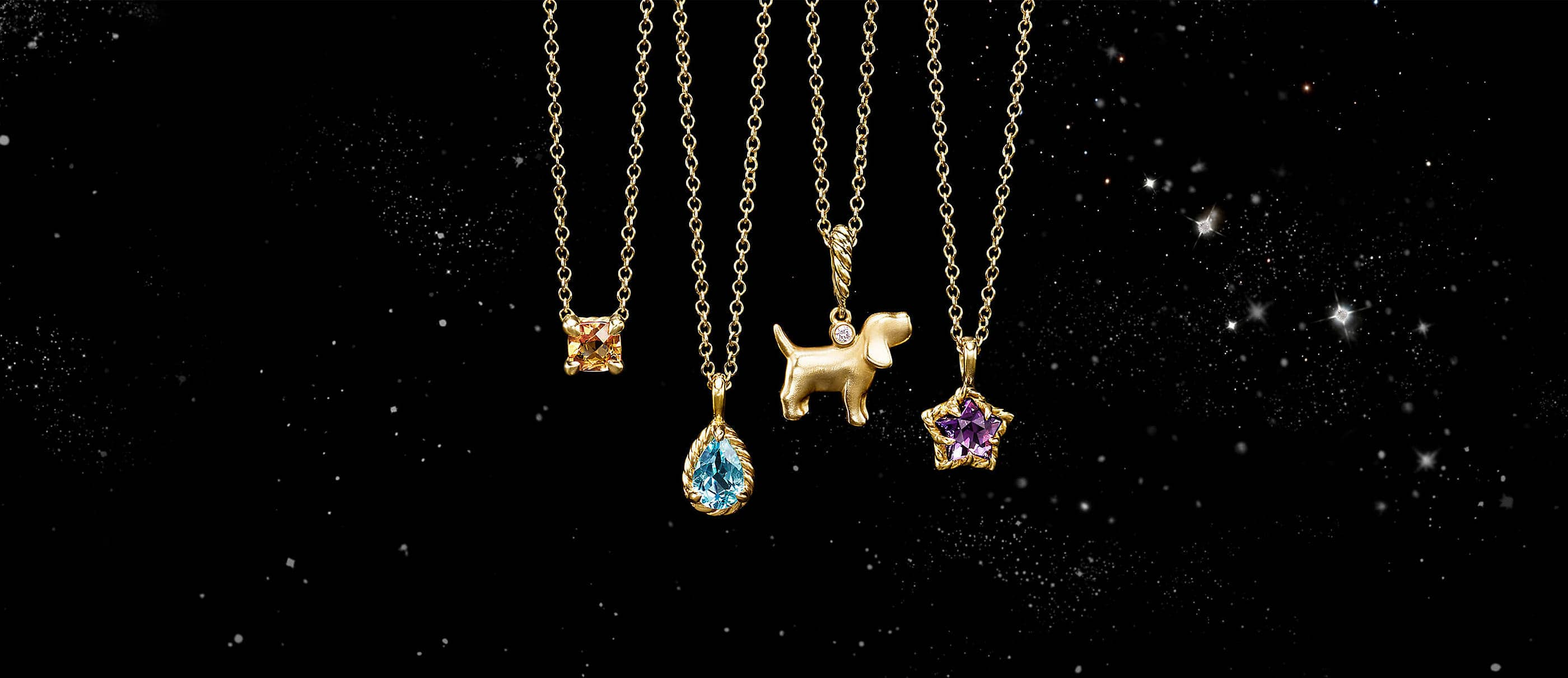 A color photograph shows four David Yurman children's pendant necklaces floating in front of a starry night sky. The necklaces are crafted from 18K yellow gold with colored gemstone pendants or a charm shaped like a dog with a single diamond.