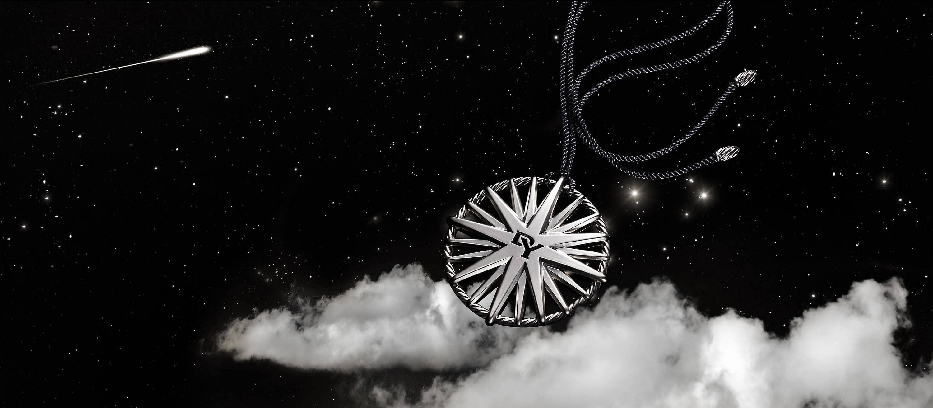 A color photo shows a silver star-shaped ornament strung on a black cord floating on a white cloud in a starry night sky.