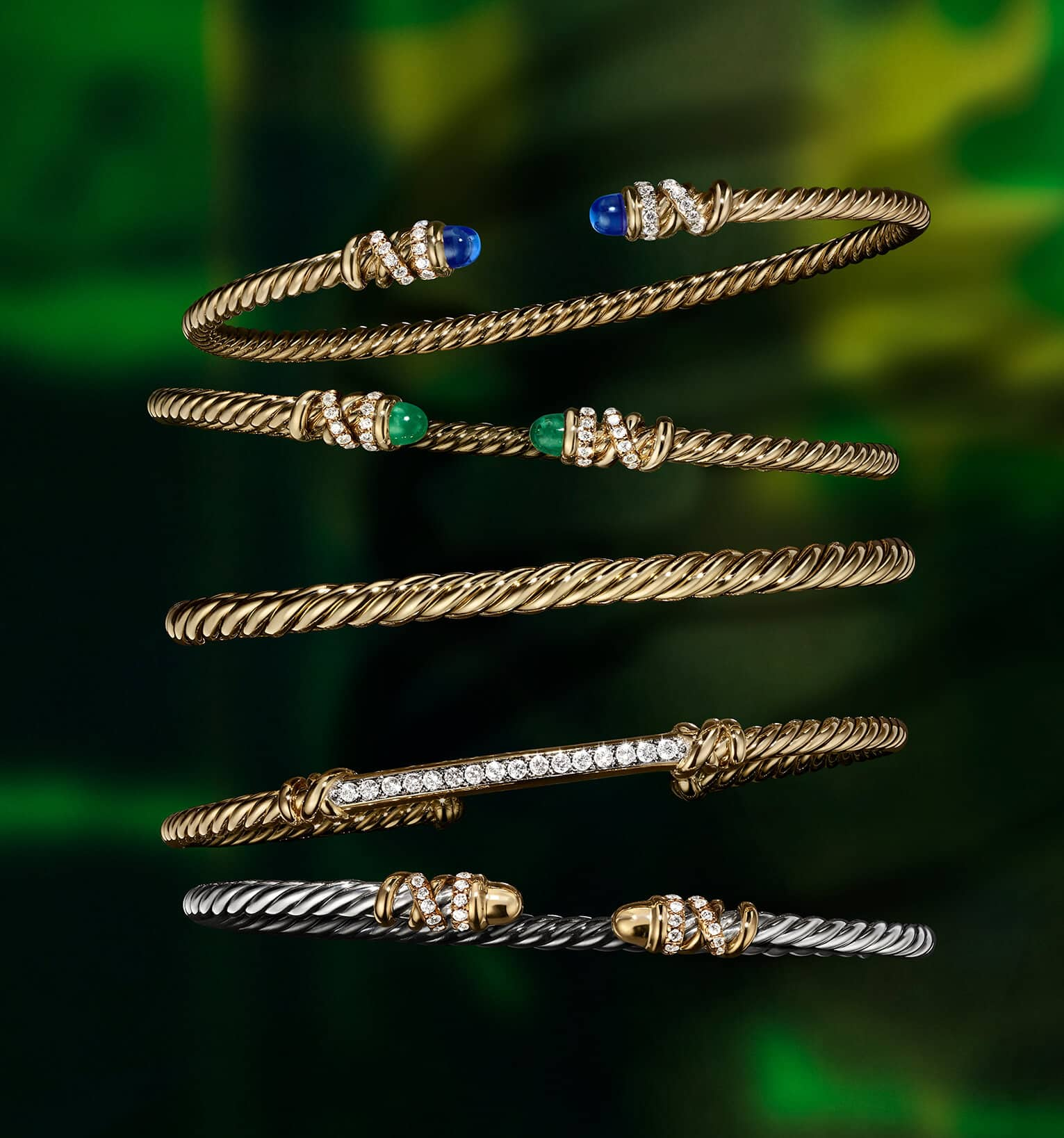 A color photo shows a vertical stack of five David Yurman bracelets for women from the Pavéflex, Modern Renaissance and Petite Pavé collections floating in front of a colorful backdrop with illuminated sections. Four of the women's bracelets are crafted from 18K yellow gold with or without pavé white diamonds. The center bracelet is crafted from 18K white gold with pavé black diamonds.