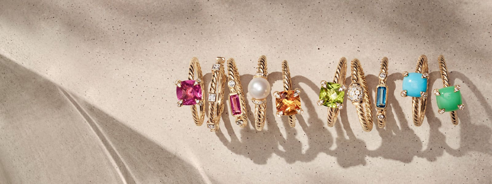 A chromatic horizontal stack of David Yurman Châtelaine®, Cable Collectibles®, Novella and Solari rings in 18K yellow gold with white diamonds and a variety of colored gemstones, standing on top of and casting long shadows on a sandy textured stone.