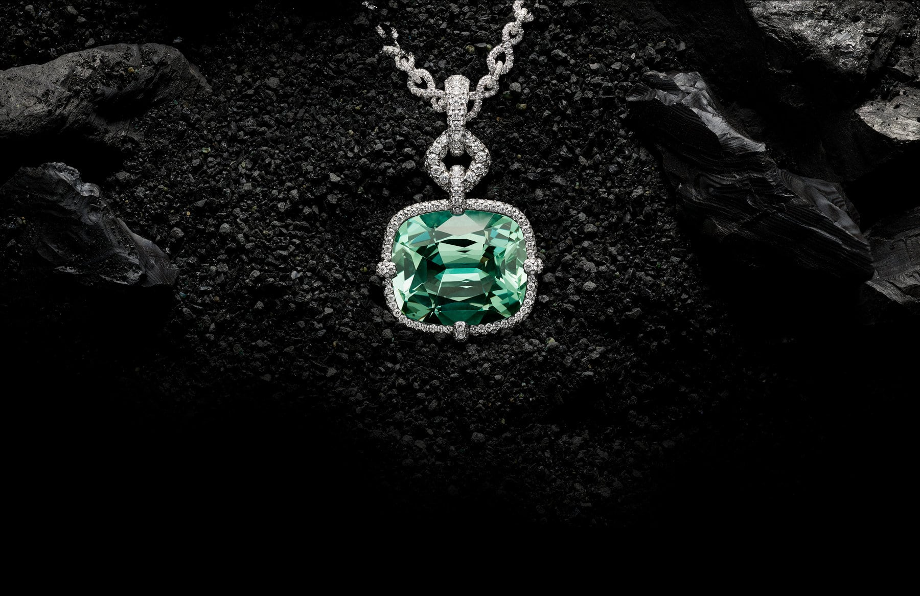 A color photo shows a David Yurman High Jewelry Gems pendant necklace shot on top of black pebbles and larger rocks. The chain necklace is crafted from 18K white gold encrusted with pavé white diamonds with a pendant of blue tourmaline.