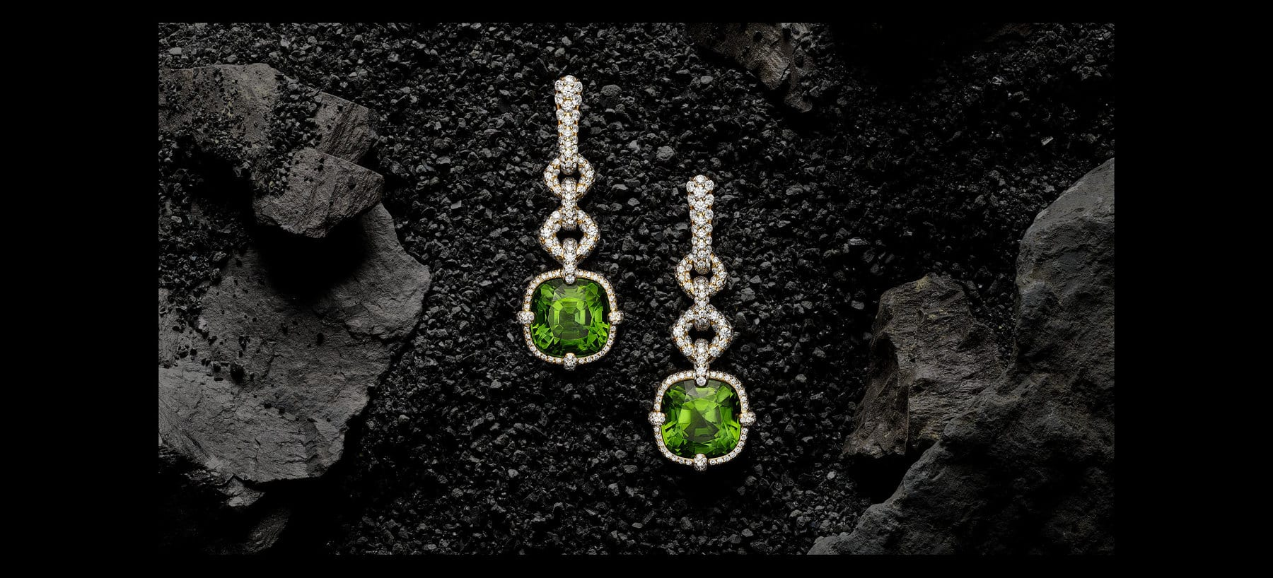 A color photo shows a pair of David Yurman High Jewelry Gems drop earrings laying at different levels from one another upright on top of a pile of small, rough, dark stones surrounded by larger dark, textured rocks. The jewelry is crafted from 18K yellow gold and is encrusted with pavé white diamonds. Two large faceted peridots are set at the end of each drop as the focal gemstones of the design.