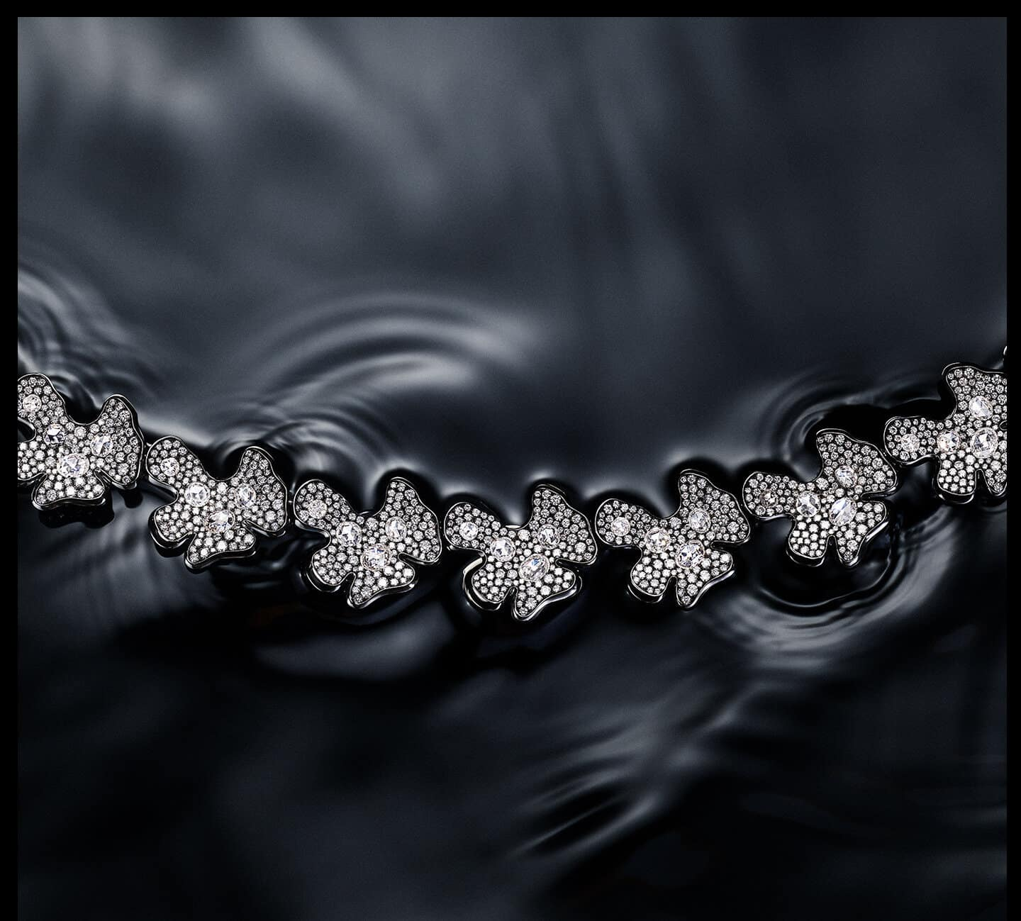 A color photo shows a David Yurman High Jewelry Petals necklace floating on water. Ripples surround the necklace, which is crafted from lily-pad-shaped stations of rhodium-plated 18K white gold encrusted with brilliant- and rose-cut white diamonds.