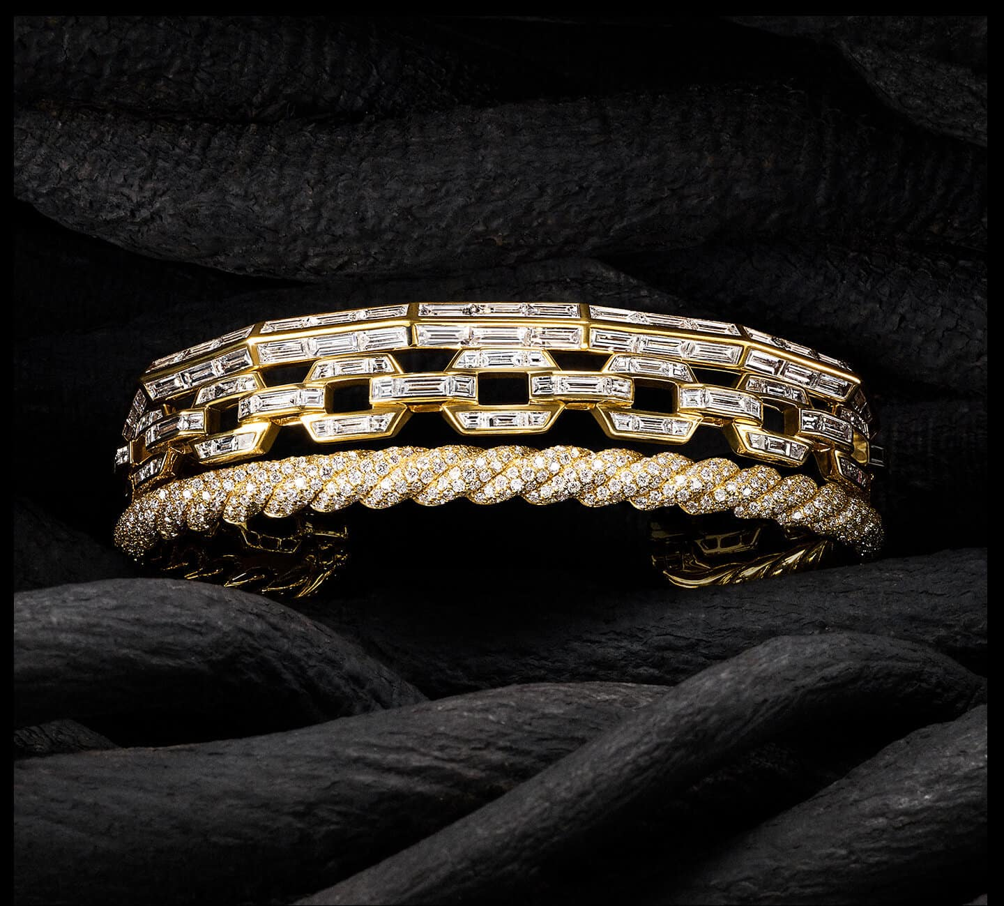 A color photo shows a David Yurman High Jewelry Stax bracelet set between thick, brown twisting tree branches reminiscent of cables. The jewelry is crafted from 18K yellow gold and is fully set with brilliant-, baguette- and custom-cut white diamonds.