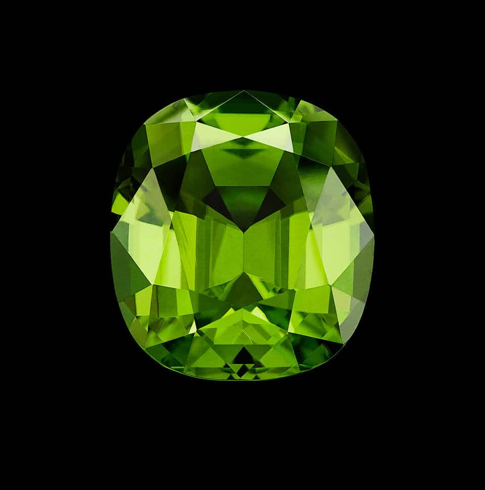 A color photo shows a loose peridot stone of exceptional size and color cut in distinct faceted shape and reflecting light.
