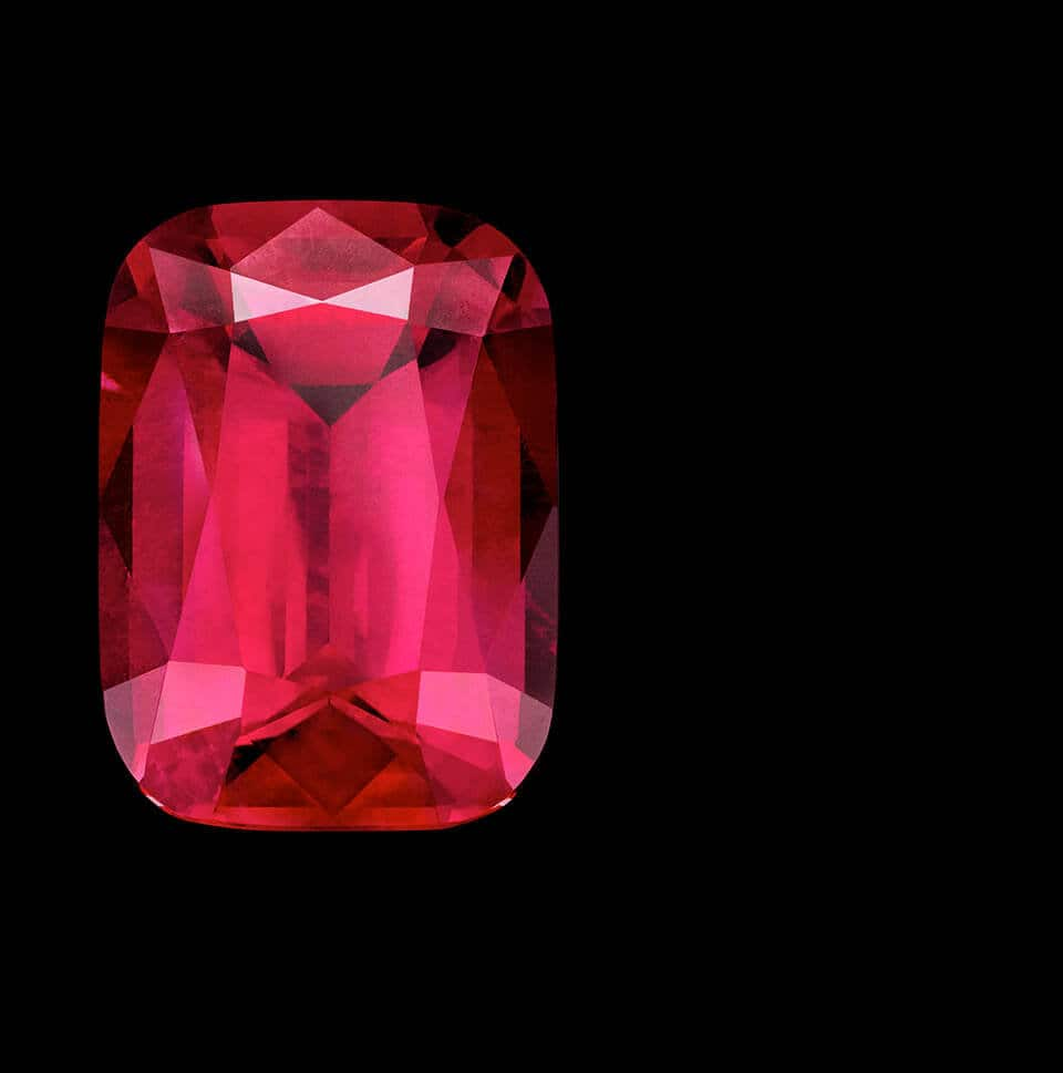 A color photo shows a loose rubellite stone of exceptional size and color cut in distinct faceted shape and reflecting light.