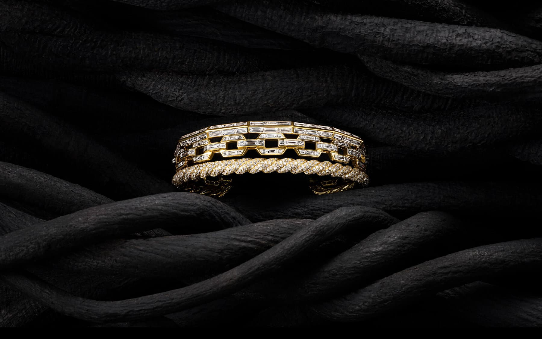 A color photo shows a David Yurman High Jewelry Stax cuff bracelet placed in between black-hued vines. The three-row cuff bracelet is crafted from 18K yellow gold encrusted with pavé and baguette white diamonds, and combines a row of faceted metal with a row of oval link chain and a row of Cable.