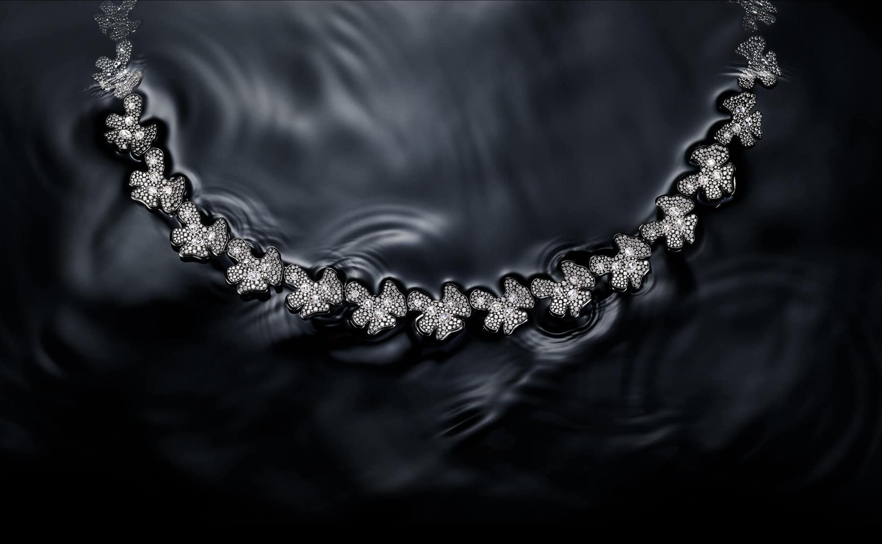 A color photo shows a David Yurman High Jewelry Petals necklace floating on water. Ripples surround the necklace, which is crafted from lily-pad-shaped stations of rhodium-plated 18K white gold encrusted with brilliant- and rose-cut white diamonds. Below the image of the necklace is another color photo showing a David Yurman Petals necklace created in the 1970s. The necklace is suspended in front of a black background reminiscent of a starry night sky. The necklace is crafted from lily-pad-shaped stations of bronze.