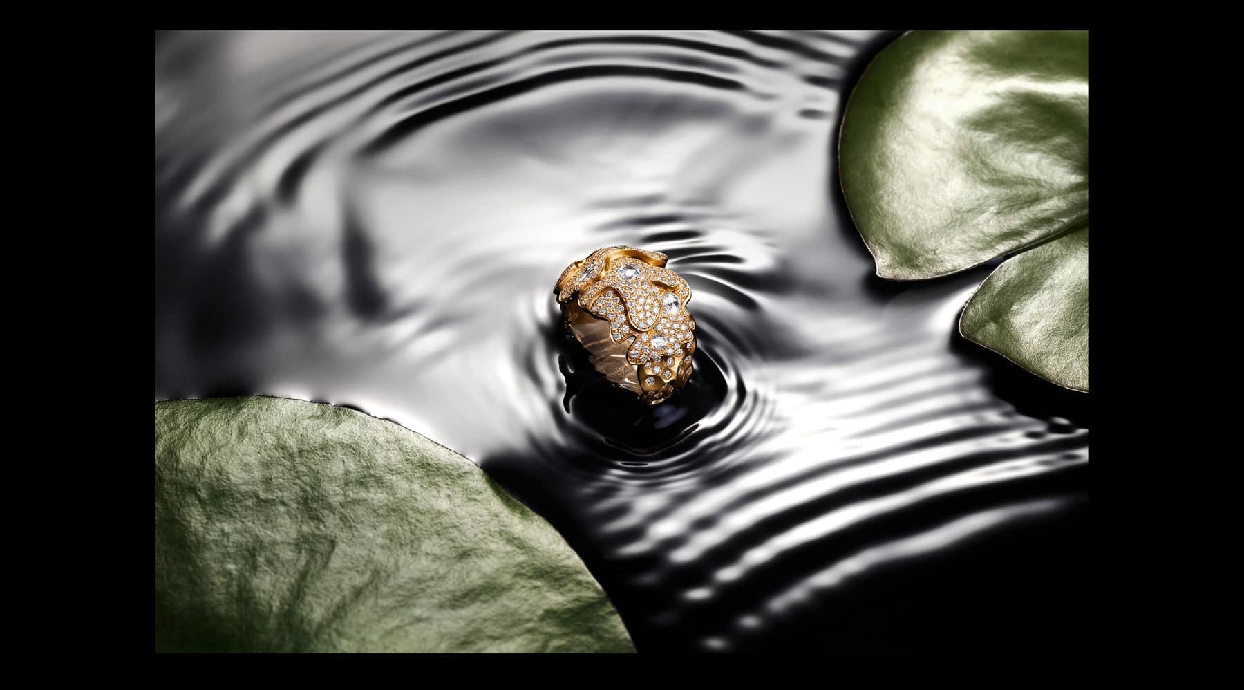 A color photo shows a David Yurman High Jewelry Day Petals ring emerging from a body of water with green lily pads. Ripples surround the ring, which is crafted from overlapping lily-pad-shaped sections of 18K yellow gold encrusted with brilliant- and rose-cut white diamonds.