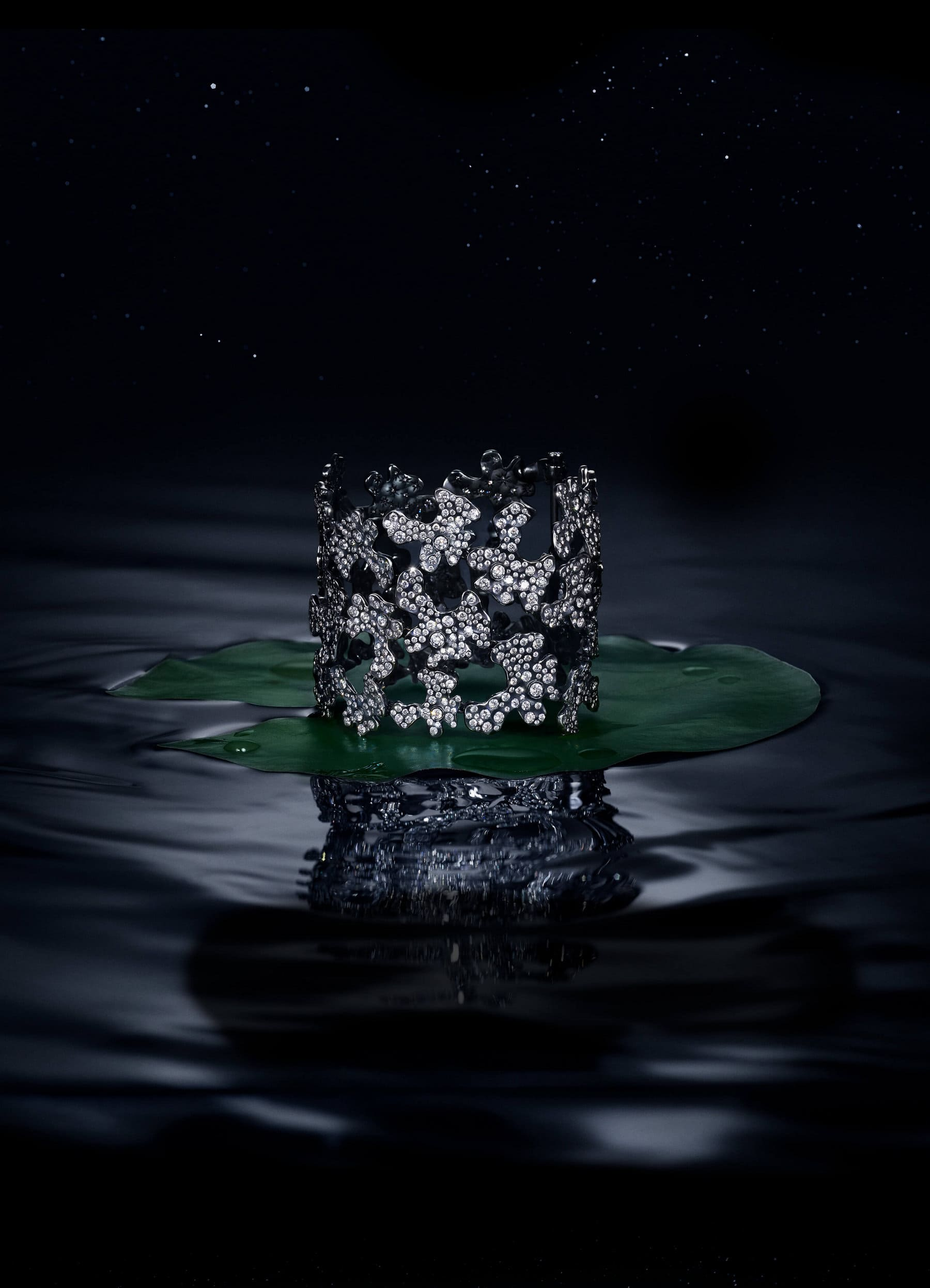 A color photo shows a David Yurman Night Petals cuff bracelet atop a green lily pad floating on a dark watery surface. The bracelet is crafted from lily-pad-shaped sections of rhodium-plated 18K white gold with brilliant- and rose-cut white diamonds.