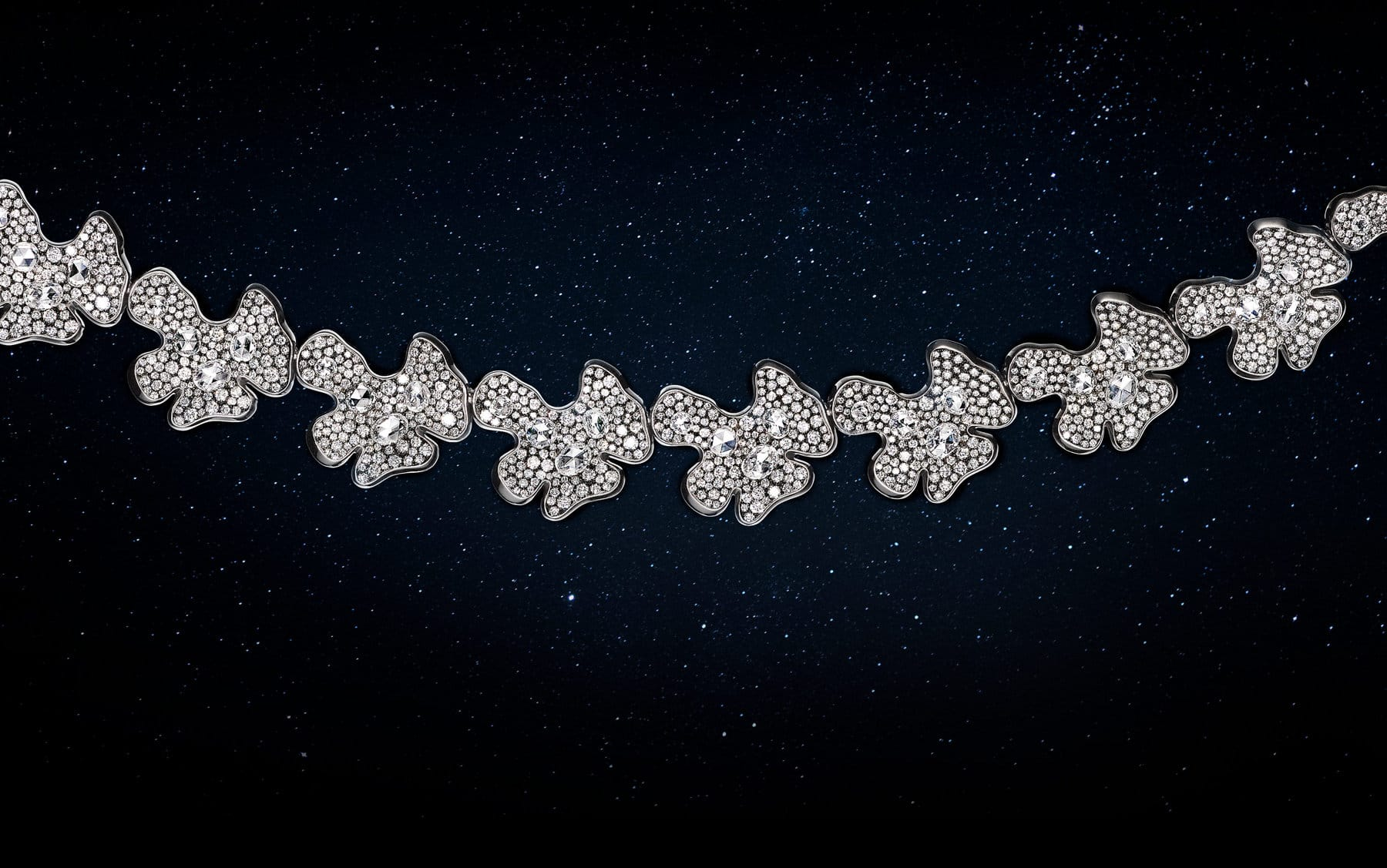 A color photo shows a close-up of David Yurman Night Petals necklace. The necklace is suspended in front of a starry night sky. The necklace is crafted from lily-pad-shaped stations of rhodium-plated 18K white gold encrusted with brilliant- and rose-cut white diamonds.