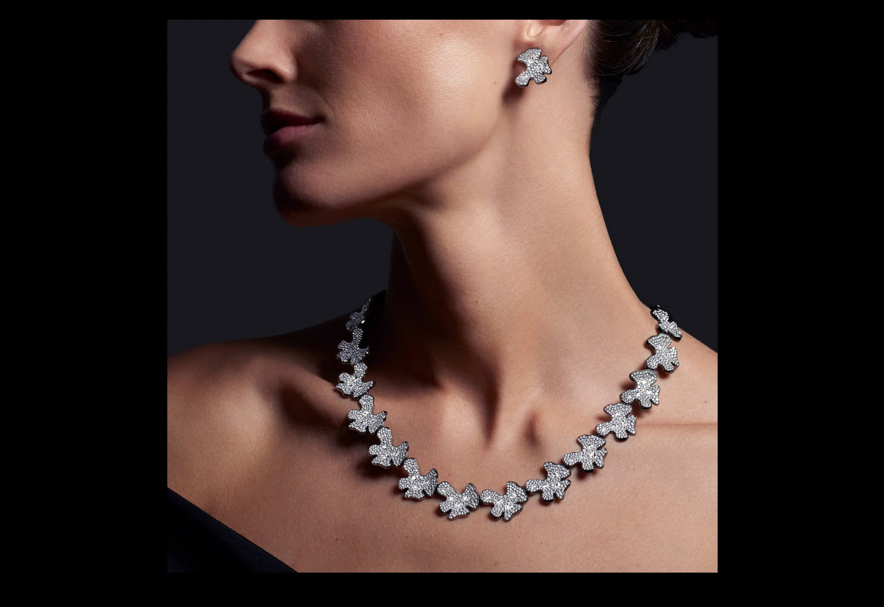 A color photo shows a model wearing a David Yurman Night Petals earring and necklace in front of a black background. The photo is cropped to show her profile from the nose down. The jewelry is crafted from lily-pad-shaped stations of rhodium-plated 18K white gold encrusted with brilliant- and rose-cut white diamonds.