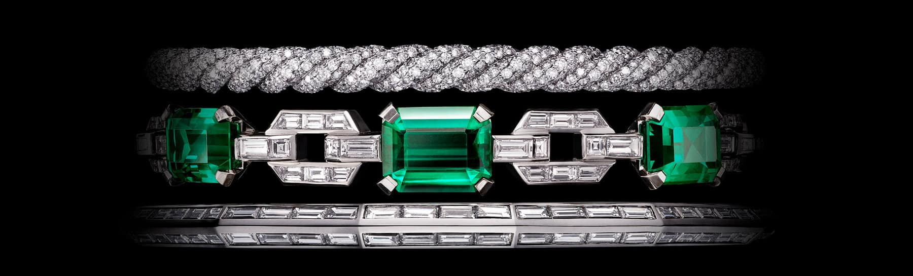 A color photo shows a close-up of the central portion of a David Yurman High Jewelry Stax three-row bracelet displayed against a black background. The jewelry is crafted from 18K white gold and is fully set with three large, emerald-cut Colombian emeralds and brilliant-, baguette- and custom-cut white diamonds.