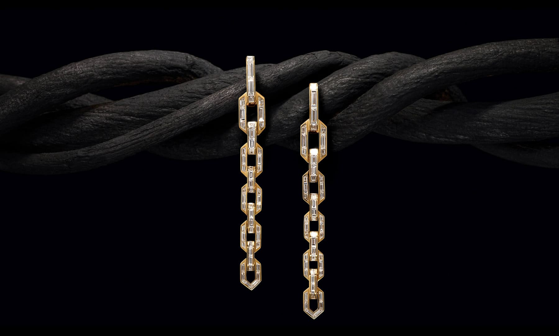 A color photo shows a pair of David Yurman High Jewelry Stax earrings hanging at different levels and superimposed over the center of a photo of a thick, brown twisted tree branch reminiscent of Cable. The jewelry is crafted from 18K yellow gold and is fully set with baguette- and custom-cut white diamonds.