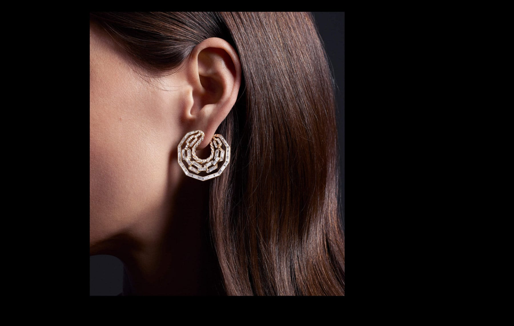 A color photo shows the side profile of a woman's head, including her left ear and straight, brown hair. Hanging from her ear is a David Yurman High Jewelry Stax hoop earrings crafted from 18K yellow gold and fully set with brilliant-, baguette- and custom-cut white diamonds.
