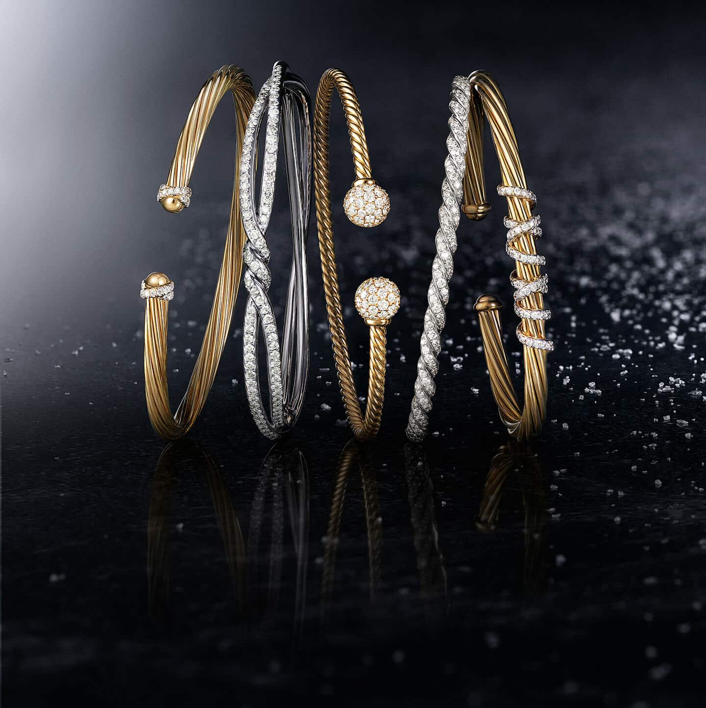 A color photo shows a horizontal stack of five David Yurman bracelets from the Helena, Continuance, Solari and Pavéflex collections leaning against each other on a black surface lightly dusted with snowflakes. The women's jewelry is crafted from 18K yellow gold with pavé white diamonds or 18K white gold with pavé white diamonds.