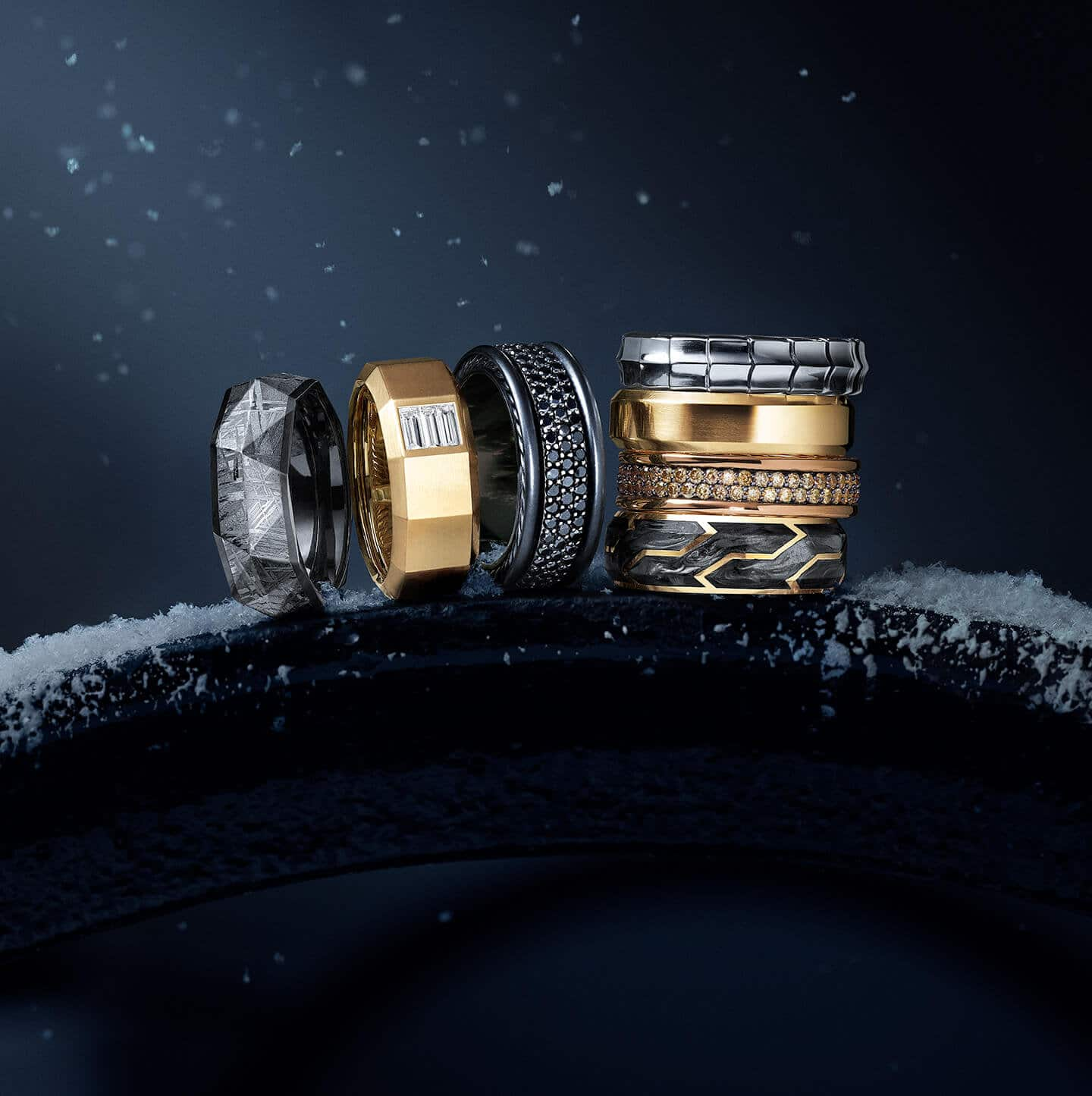 A color photograph shows a horizontal stack of three David Yurman Men's band rings atop a snow-dusted metal ledge at night. Next to the rings are a stack of four David Yurman Men's band rings. The jewelry is crafted from meteorite with black titanium, 18K yellow gold with baguette white diamonds, black titanium with pavé black diamonds and sterling silver, 18K white gold, 18K yellow gold, 18K rose gold with pavé cognac diamonds or forged carbon with 18K yellow gold.