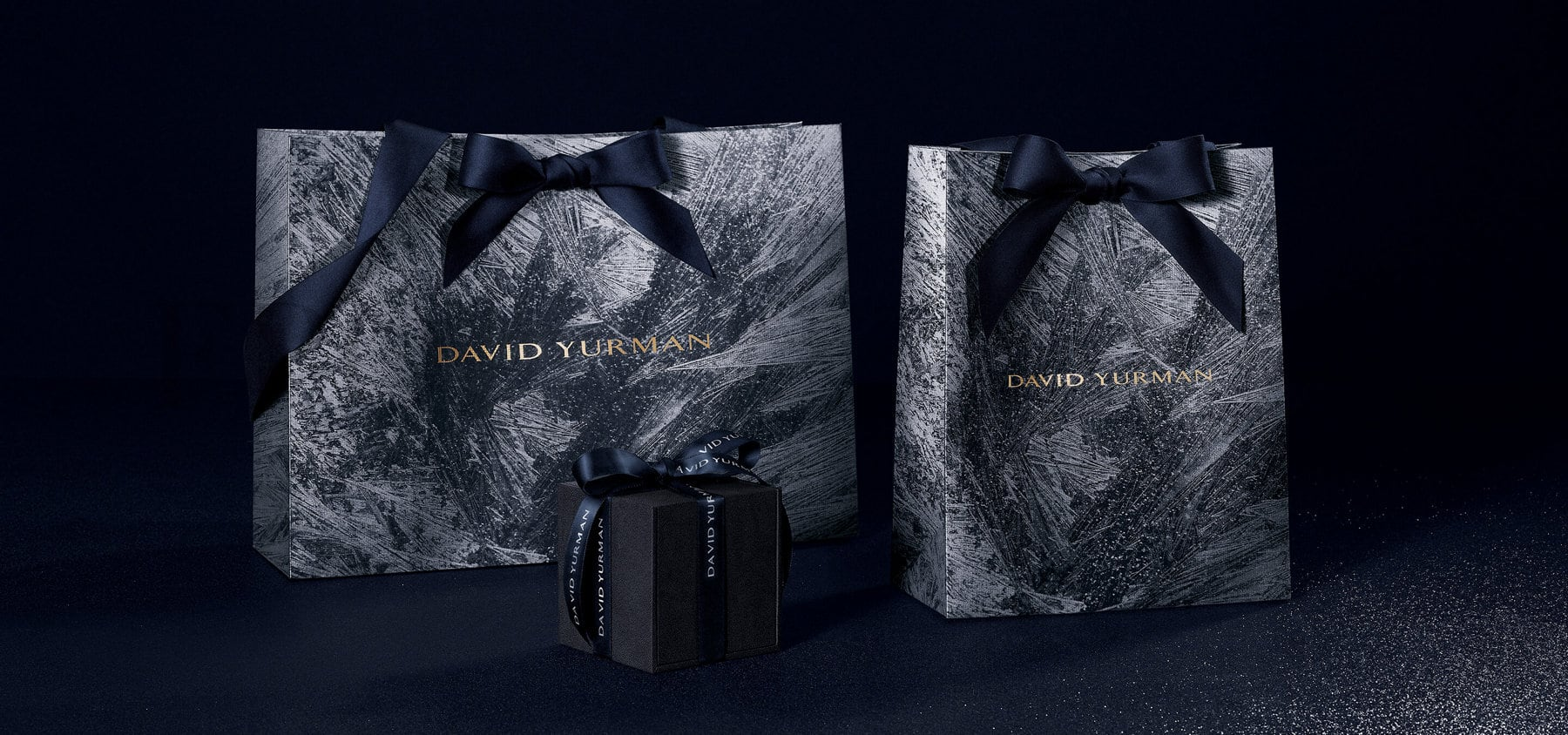 A color photo shows large and small David Yurman gift bags standing behind a David Yurman ring box on a glittery black surface. The gift bags feature navy-hued bows at the top and are covered with a silvery frost-inspired pattern on a dark grey background. The David Yurman logo is printed in gold in the center of each bag. The black ring box is wrapped with a black ribbon featuring the David Yurman logo printed in white.