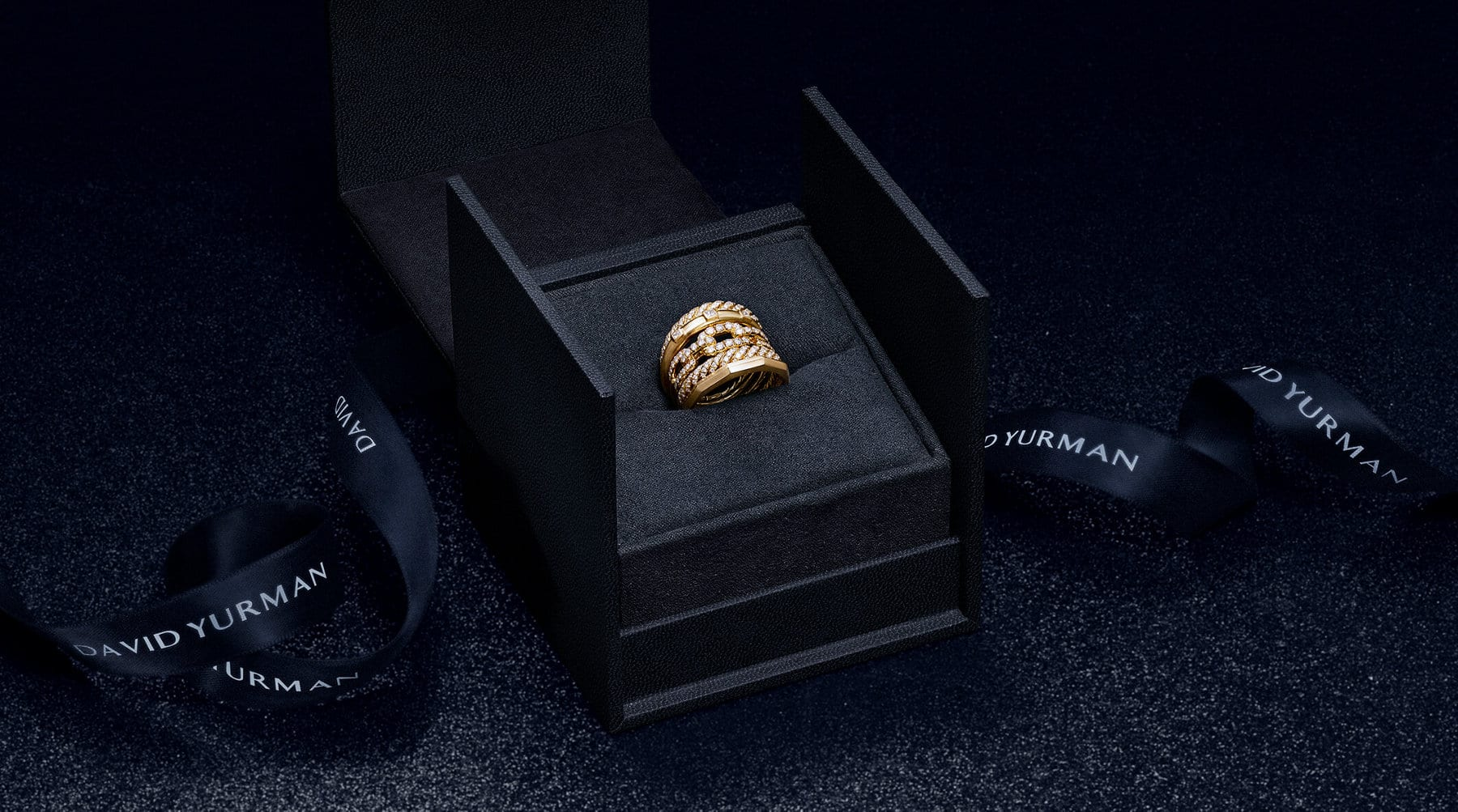 A color photo shows a black ring box open revealing a David Yurman women's Stax ring inside. Featuring the David Yurman logo printed in white, a winding black ribbon is placed next to the box on a glittery black surface. The ring is crafted from five rows of 18K yellow gold with pavé white diamonds, combining strands of Cable, faceted metal, link chain and smooth metal, creating the look of multiple rings stacked together.