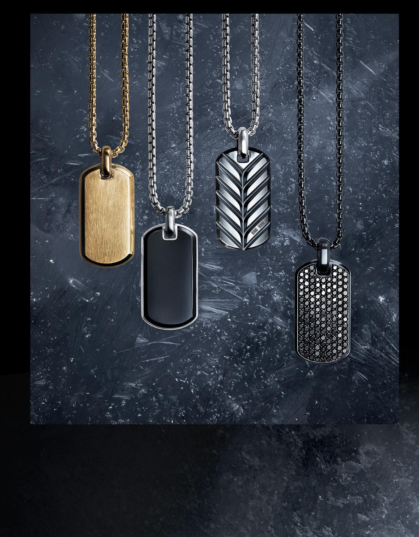 A color photo shows a row of four David Yurman men's tags strung on Chain necklaces and laying at different levels atop a dark, icy surface dusted with snowflakes. The jewelry is crafted from 18K yellow gold, sterling silver or black titanium. From left is a Streamline tag, an Exotic Stone tag with black onyx, a Streamline tag sculpted with Chevron motifs and a Pavé tag with pavé black diamonds.