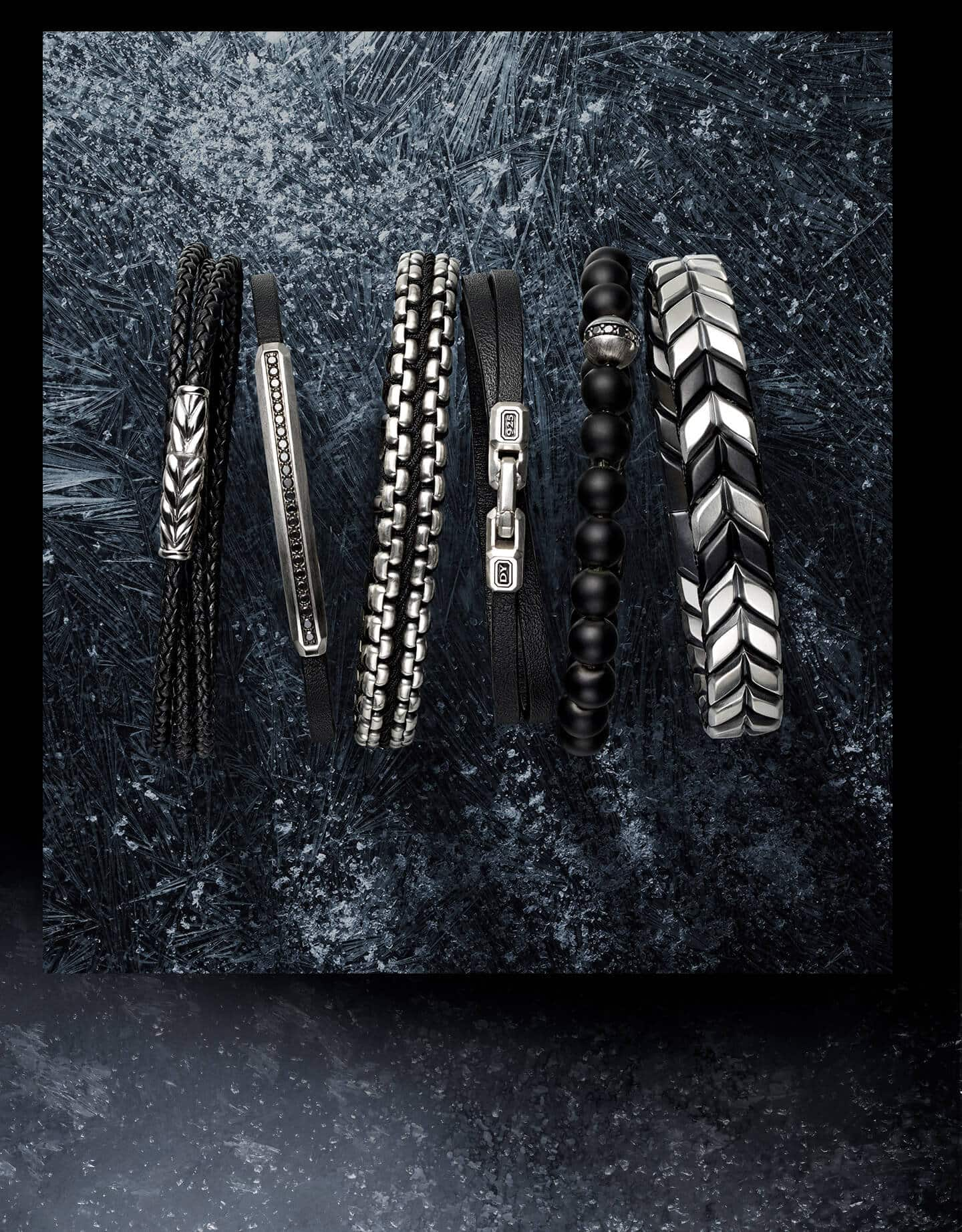 A color photo shows six David Yurman men's bracelets crafted from sterling silver and arranged in a row on top of a dark, scratched, snow-dusted icy surface as seen from above. From left is a Chevron triple-wrap bracelet in braided black leather, a Streamline ID bracelet in black leather with pavé black diamonds, a Chain bracelet in black nylon, a Streamline double-wrap bracelet in black leather, a Spiritual Beads bracelet in black onyx with pavé black diamonds and a Chevron bracelet with black titanium.