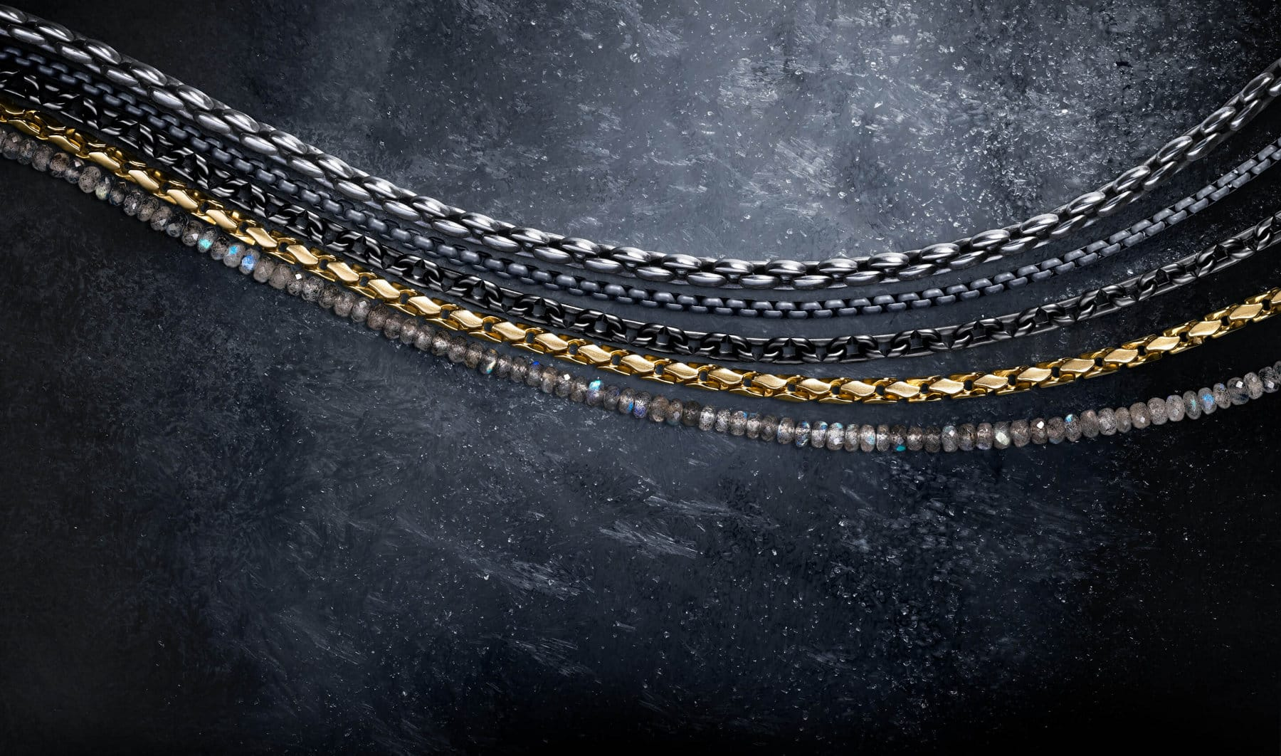 A color photo shows four David Yurman men's necklaces from the Chain and Spiritual Beads collections arranged in rows next to each other atop a snow-dusted dark, icy surface. The Chain necklaces are crafted from sterling silver, grey stainless steel or black titanium with sterling silver, and from 18K yellow gold. The Spiritual Beads necklace is crafted from labradorite with sterling silver.
