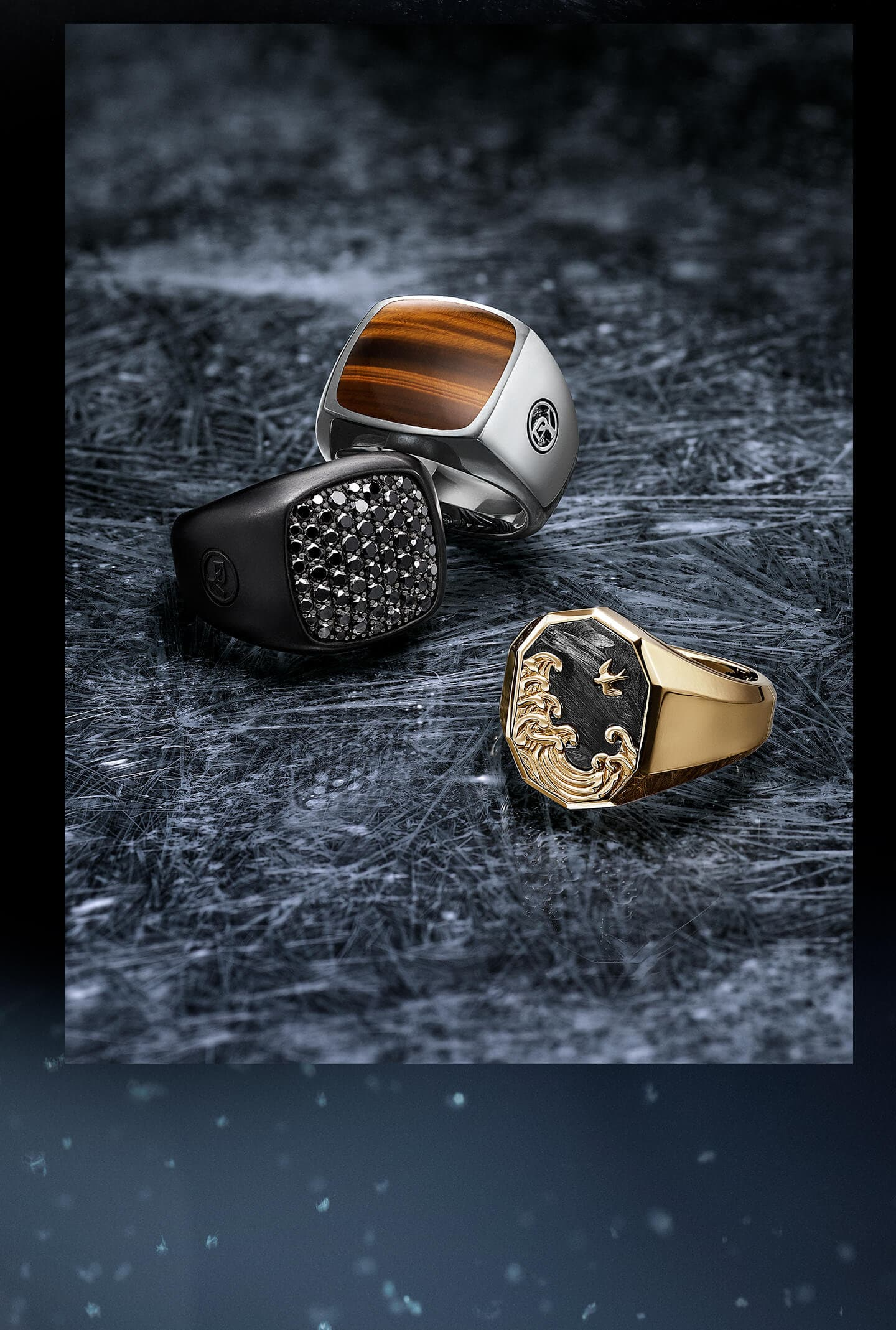 A color photo shows 3 David Yurman men's signet rings from the Exotic Stone, Pavé and Waves collections arranged on top of a snow-dusted dark, scratched, icy surface. The Exotic Stone ring is crafted from sterling silver with tiger's eye, and is leaning up and against the Pavé ring, which is crafted from black titanium with pavé black diamonds. The Waves ring situated in front and slightly to the right of the other rings, facing them, and is crafted from 18K yellow gold with forged carbon.