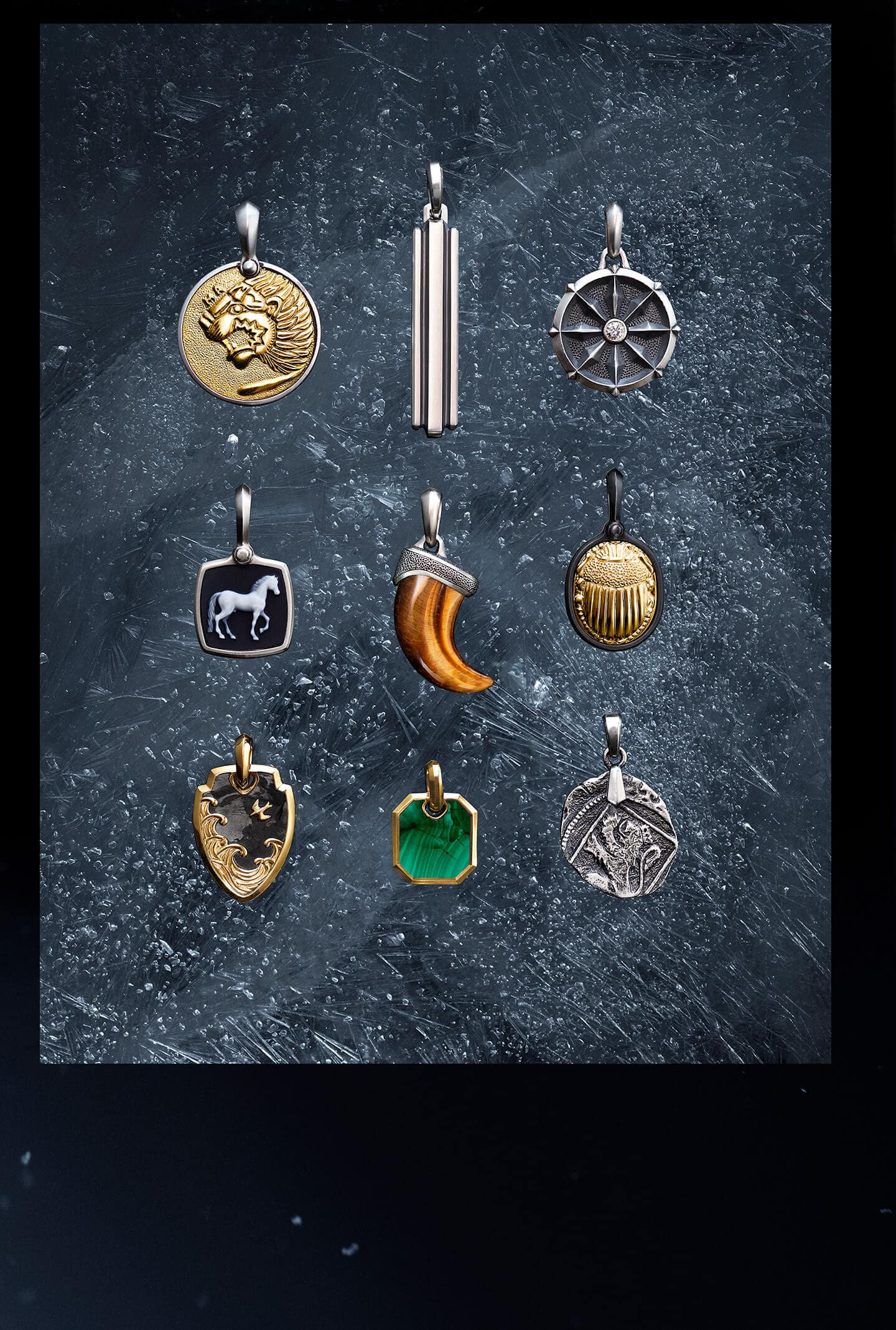 A color photo shows a three-by-three grid of nine David Yurman men's amulets laying atop a dark, icy surface dusted with snowflakes. The jewelry is crafted from sterling silver, black titanium or 18K yellow gold. In the top row, from left, is a Petrvs lion amulet with 18K gold, a Deco ingot tag and a Maritime wheel with a reverse-set white diamond. In the middle row, from left, is a Petrvs horse amulet with banded agate, a claw amulet in tiger's eye and a Petrvs scarab amulet with 18K gold. In the bottom row, from left, is a Waves shield amulet with forged carbon, a Roman amulet with malachite and a Shipwreck coin amulet.