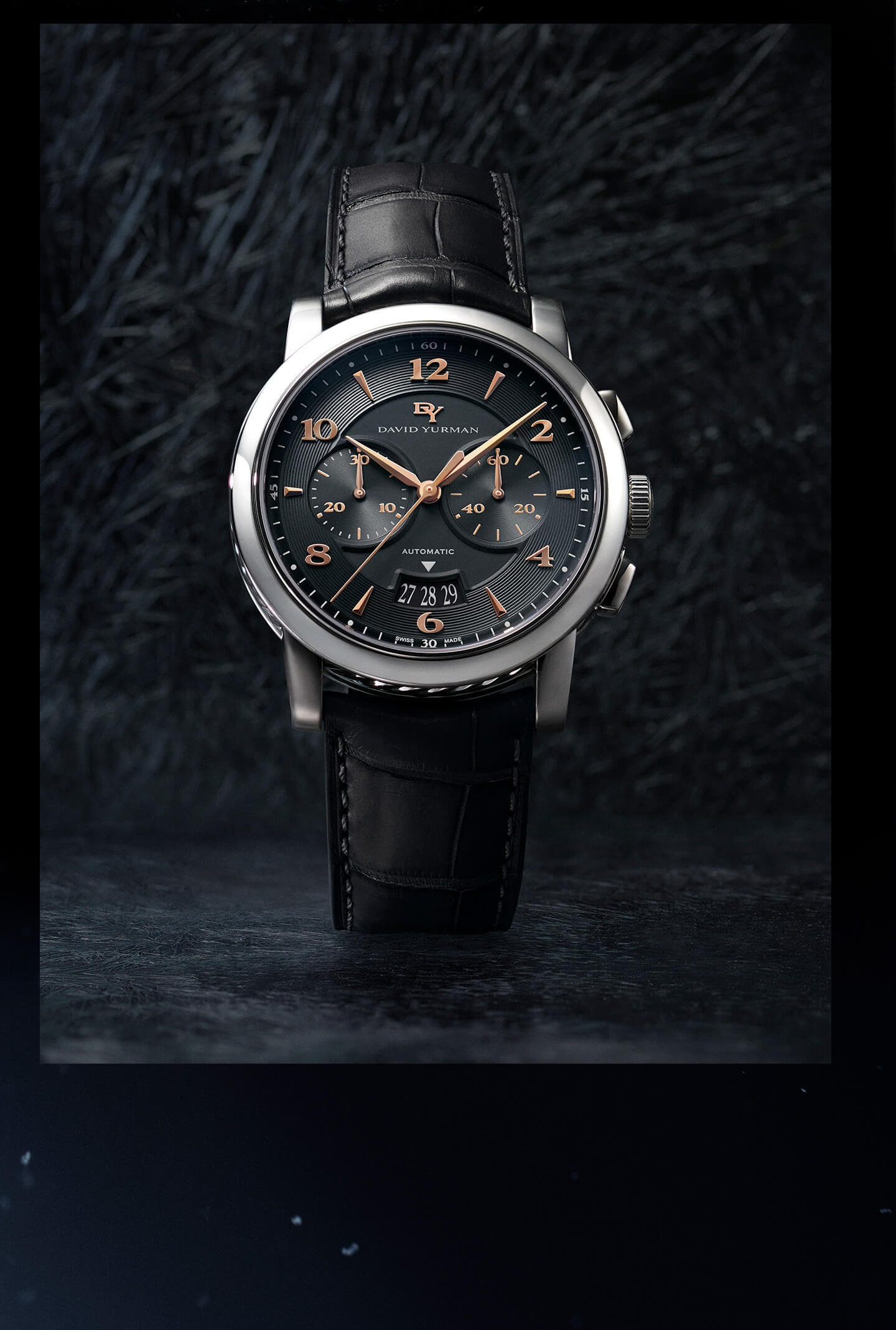 A color photo shows a David Yurman men's Classic 43.5mm chronograph watch standing upright atop and in front of dark, rough, scratched and icy surfaces. The timepiece is crafted with an anthracite matte alligator strap and a Cable-detailed stainless-steel case featuring a Swiss automatic chronograph movement.