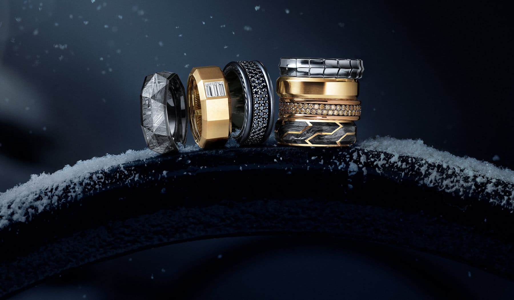 A color photo shows 7 David Yurman men's band rings in a ray of light on top of the snow-covered metal railing of a bench. Three rings in total from the Faceted and Pavé collections are standing upright in a row next to four rings in total from the Armory, Beveled, Streamline and Forged Carbon collections, which are stacked vertically on top of one another. The Faceted rings are crafted from black titanium with faceted meteorite or from 18K yellow gold with baguette white diamonds. The Pavé ring is crafted from black titanium with black diamonds. The Armory ring is crafted from 18K white gold. The Beveled ring is crafted from 18K yellow gold. The Streamline ring is crafted from 18K rose gold with pavé cognac diamonds. The Forged Carbon ring is crafted from 18K yellow gold with forged carbon.