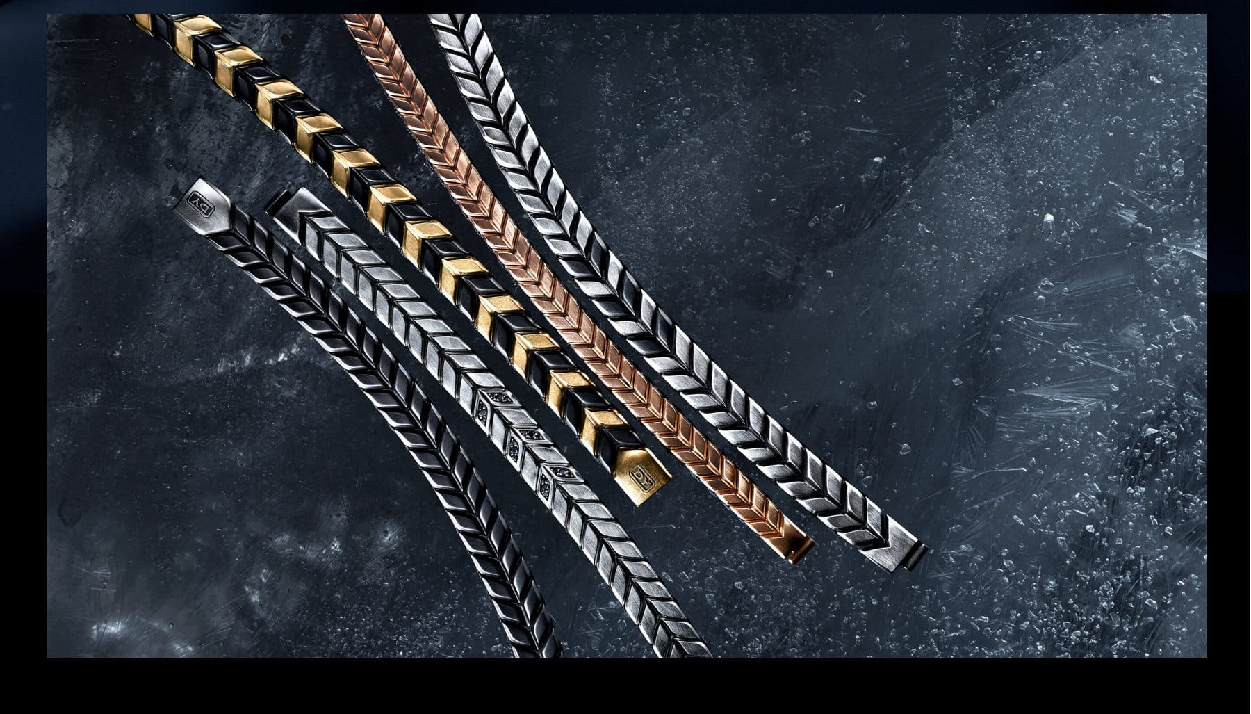 A color photo shows 5 David Yurman men's Chevron bracelets arranged in rows next to each other atop a snow-dusted dark, icy surface. The bracelets are crafted from black titanium with sterling silver, sterling silver with pavé black diamonds, 18K yellow gold and black titanium, 18K rose gold or sterling silver with black titanium.