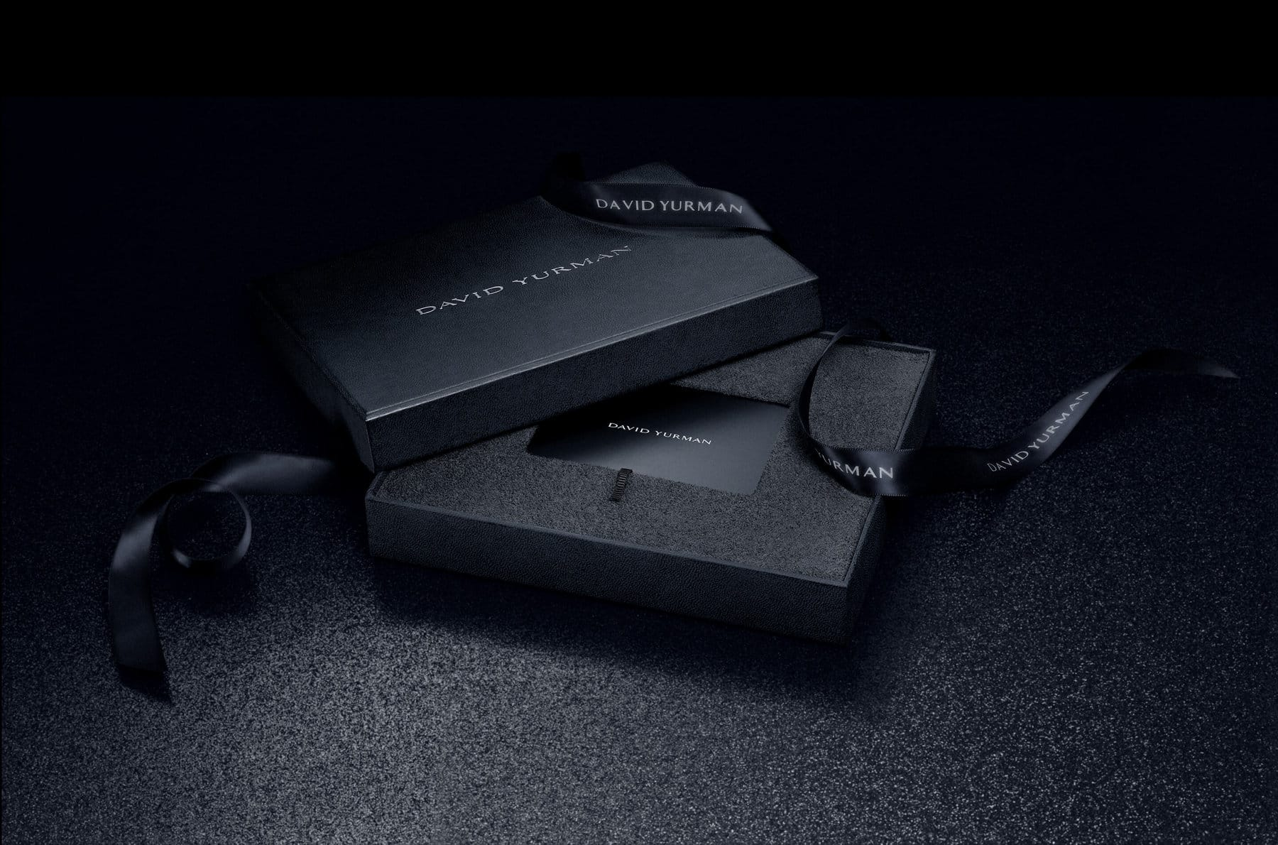 A color photograph shows a black gift card displaying only the David Yurman logo in white set inside a David Yurman gift box draped with a navy David Yurman ribbon. The packaging and gift card are shown in a ray of light on top of a black stone surface.