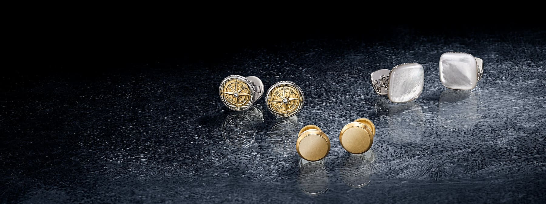 A color photograph shows three pairs of David Yurman men's cufflinks arranged in a horizontal group on top of a crystalline, icy surface with reflections of the jewelry. From left are Maritime compass cufflinks in sterling silver with 18K gold and white diamonds and Streamline cufflinks in 18K gold or sterling silver with mother-of-pearl.