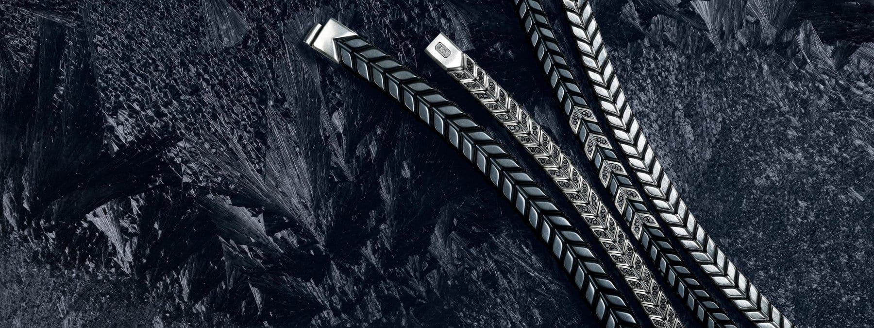 A color photograph shows a diagonal row of four David Yurman men's Chevron bracelets laying on top of a dark, icy surface dusted with snowflakes. The bracelets are crafted from black titanium with sterling silver, sterling silver with or without black diamonds and black titanium with sterling silver and black diamonds.