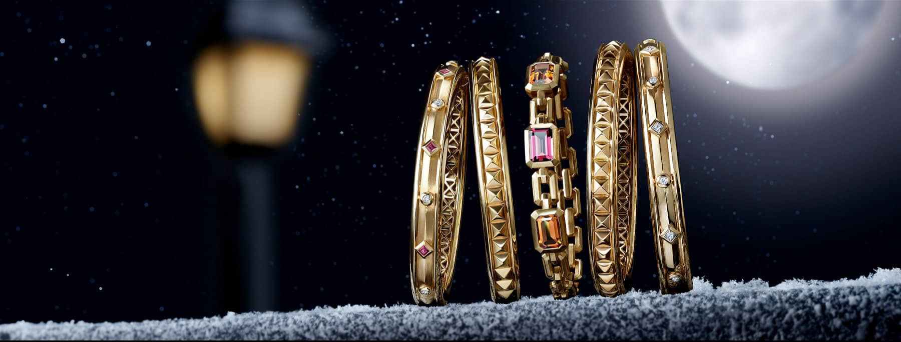 Five David Yurman bracelets from the Renaissance and Novella collections are leaning against each other at night on a stone ledge lightly dusted with snowflakes. The women's jewelry is crafted from 18K yellow gold with or without white diamonds, rubies, citrine or pink tourmaline. In the dark background is the golden glow of a nearby street light.