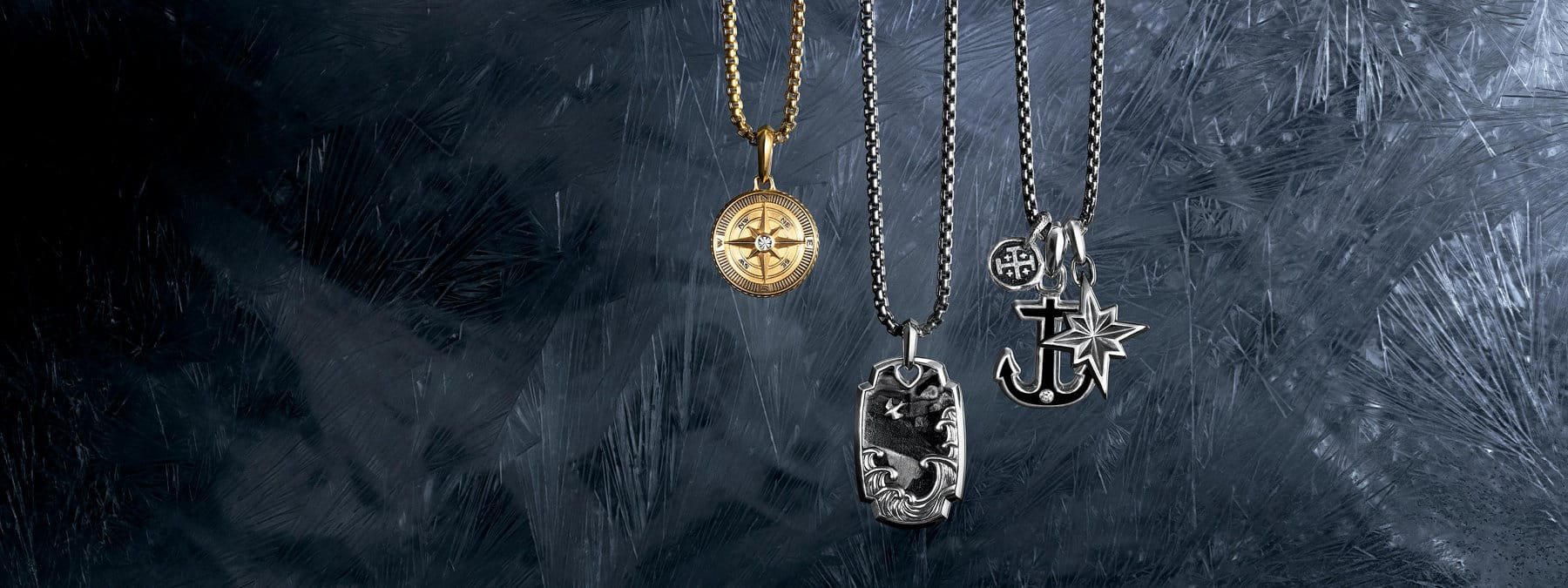 A color photo shows three David Yurman men's box-chain necklaces in 18K yellow gold or sterling silver arranged in a row atop a dark, scratched icy surface dusted with snowflakes. Each necklace is strung with one or three David Yurman men's amulets crafted from 18K yellow gold or sterling silver. From left is a Maritime compass with a single white diamond, a Waves tag with forged carbon, a Shipwreck coin amulet, a Maritime anchor with black onyx and a single white diamond and a Maritime North Star amulet.