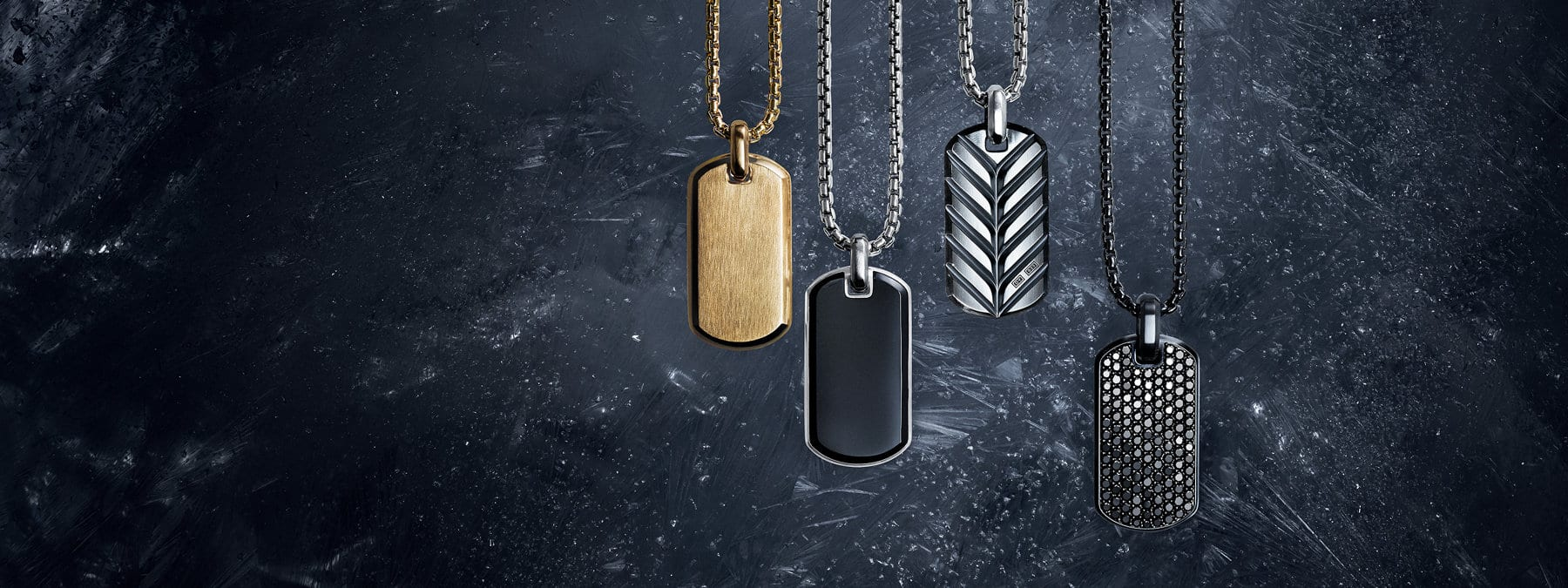 A color photograph shows a horizontal row of four David Yurman men's tags from the Streamline, Exotic Stone, Chevron and Pavé collections hanging on box-chain necklaces at different levels in front of a dark, icy surface dusted with snow. The tags are crafted from 18K yellow gold, sterling silver with or without black onyx and black titanium with pavé black diamonds. The chains are crafted from 18K yellow gold, sterling silver or black titanium.