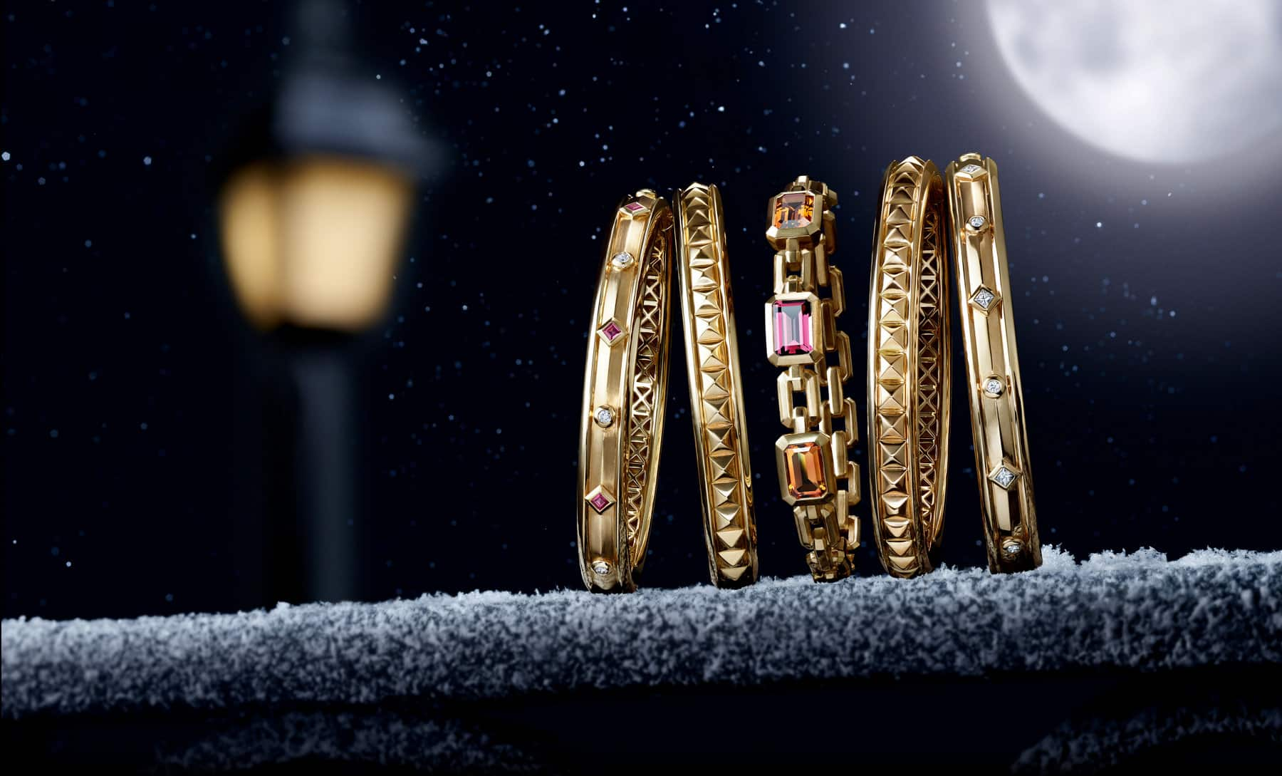 Five David Yurman bracelets from the Renaissance and Novella collections are leaning against each other at night on a stone ledge lightly dusted with snowflakes. The women's jewelry is crafted from 18K yellow gold with or without white diamonds, rubies, citrine or pink tourmaline. In the dark background is the golden glow of a nearby street light and a full moon.