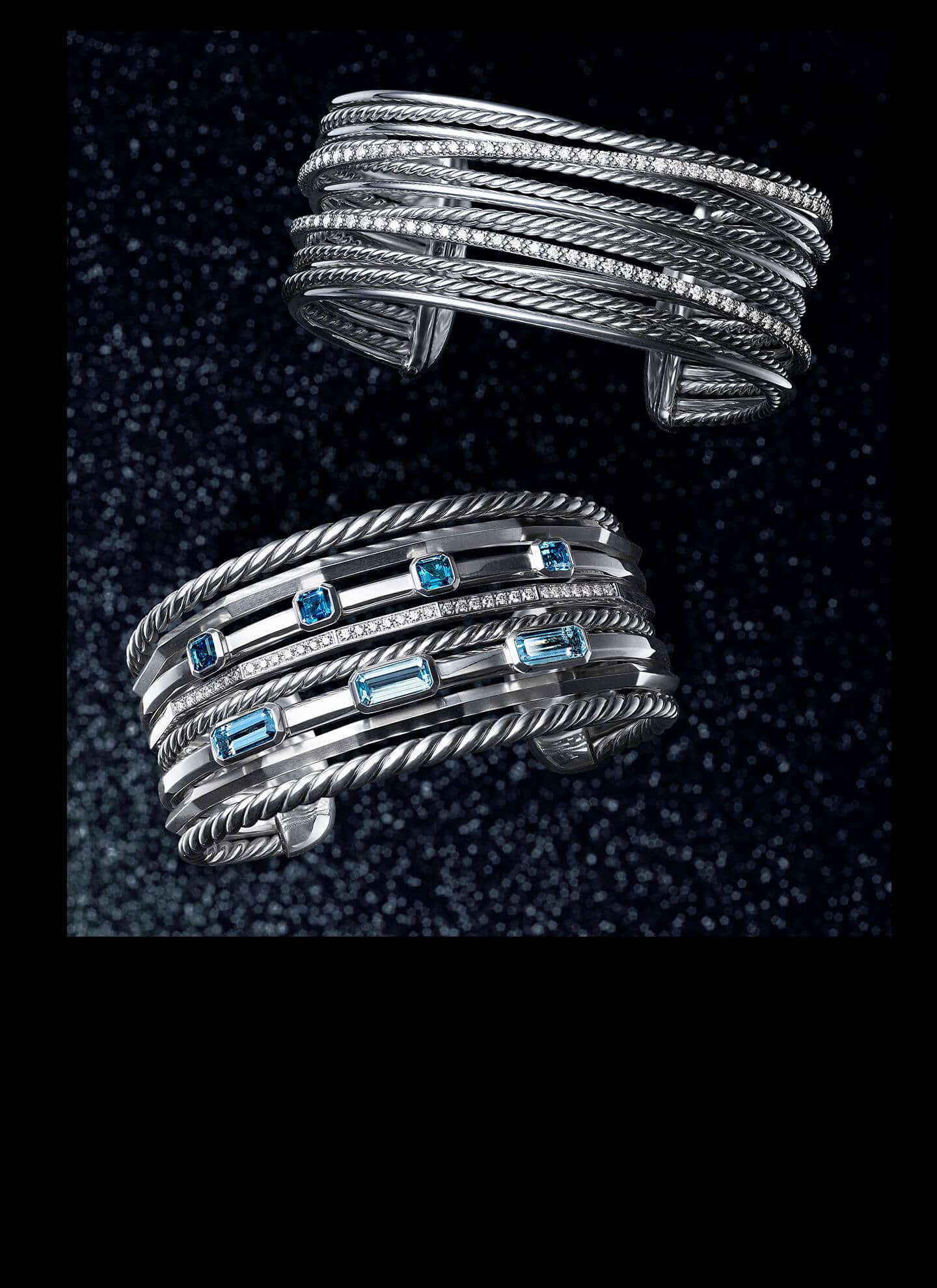 A David Yurman Stax cuff bracelet is placed below a David Yurman Crossover cuff bracelet. Both women's bracelets are crafted from sterling silver with white diamonds and with or without blue topaz, and placed atop a black glittery background.