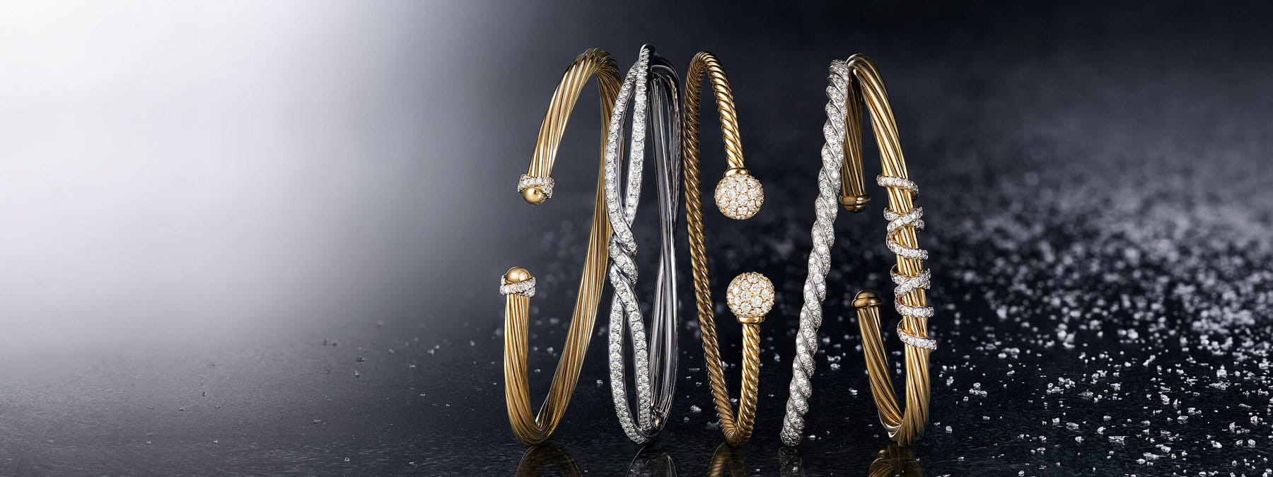 A color photo shows a horizontal stack of five David Yurman bracelets from the Helena, Continuance, Solari and Pavéflex collections leaning against each other on a black surface lightly dusted with snowflakes. Three of the women's bracelets are crafted from 18K yellow gold with threads or spheres encrusted with pavé white diamonds. Two of the women's bracelets are crafted from 18K white gold encrusted with pavé white diamonds.
