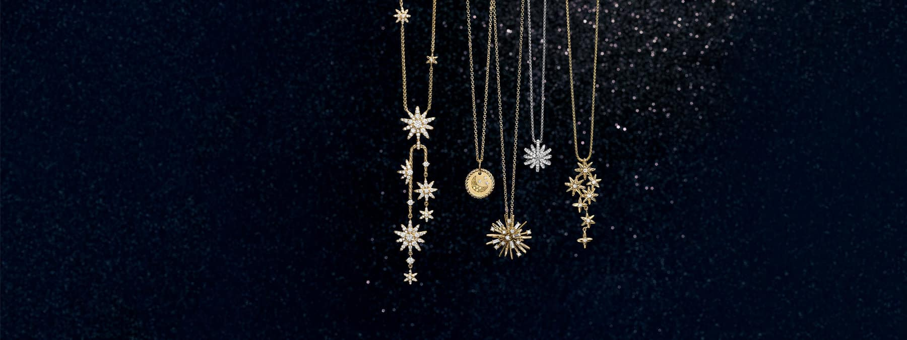 A color photo shows five David Yurman star-shaped or celestial necklaces for women from the Starburst, Cable Collectibles and Supernova collections suspended before a black glittery backdrop. Second from the left is a Cable Collectibles necklace whose charm features a yellow sapphire crescent moon and pavé diamond stars. The women's necklaces are crafted from 18K yellow gold with pavé white diamonds or 18K white gold with pavé white diamonds.