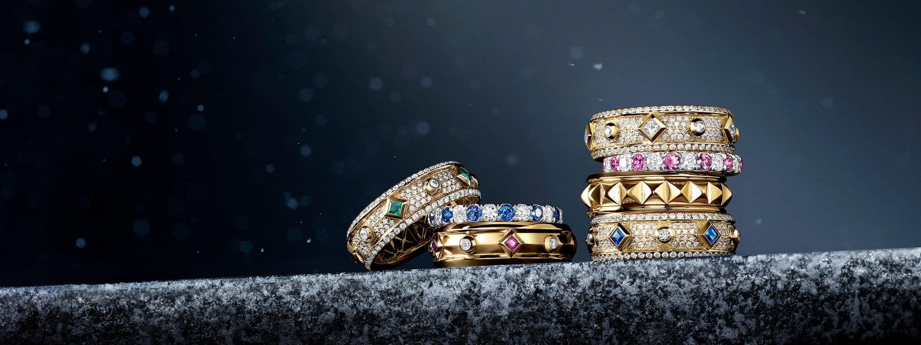 A color photograph shows two vertical stacks of David Yurman band rings from the Renaissance and DY Eden collections. The women's jewelry is crafted from 18K yellow gold with or without white diamonds, emeralds, blue or pink sapphires, or rubies, and photographed atop a snow-dusted stone ledge at night.