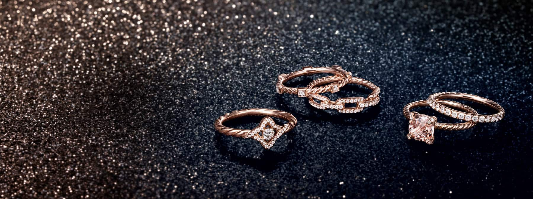 A color photograph shows five David Yurman rings scattered on top of a black glittery surface. The jewelry is crafted from 18K rose gold with or without morganite and pavé white diamonds.