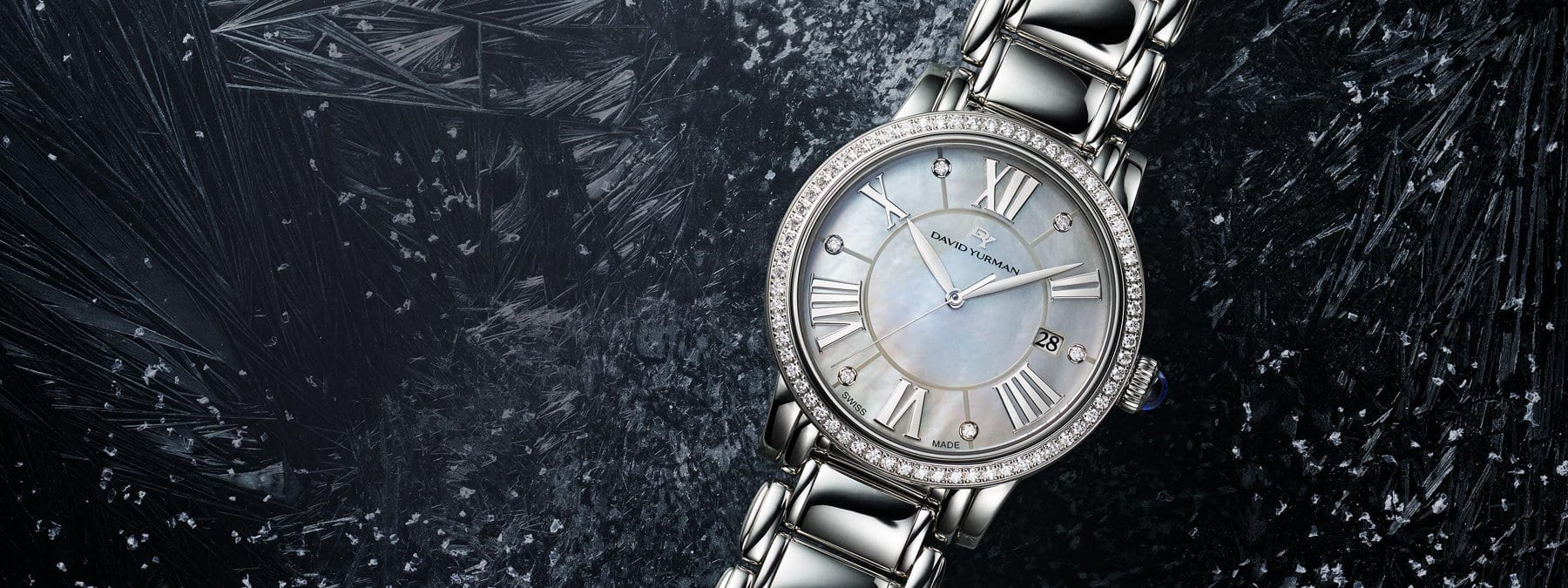 A color photograph shows a close-up of a David Yurman Classic women's watch atop a dark ice-covered surface. The bracelet watch is crafted from stainless steel with a ring of pavé diamonds around its mother-of-pearl face and six white diamonds set between roman numerals on its face.