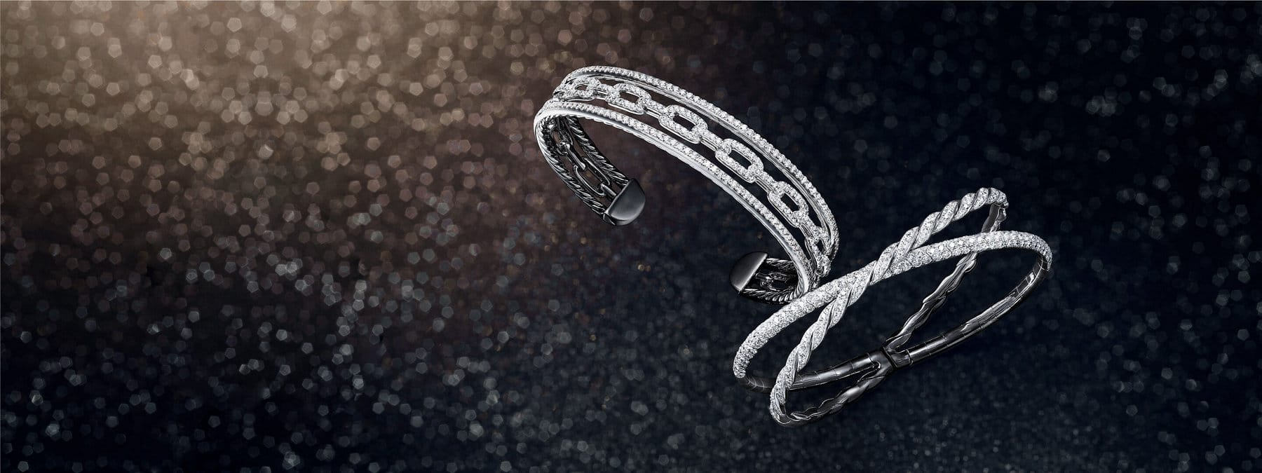 A color photo shows three David Yurman Pavéflex cuff bracelets for women scattered from a black glittery background. The women's cuff bracelets combine multiple rows of Cable with rows of pavé white diamonds, creating the look multiple bracelets in one. The jewelry is crafted from 18K white and rose gold, 18K white gold or 18K white, yellow and rose gold.