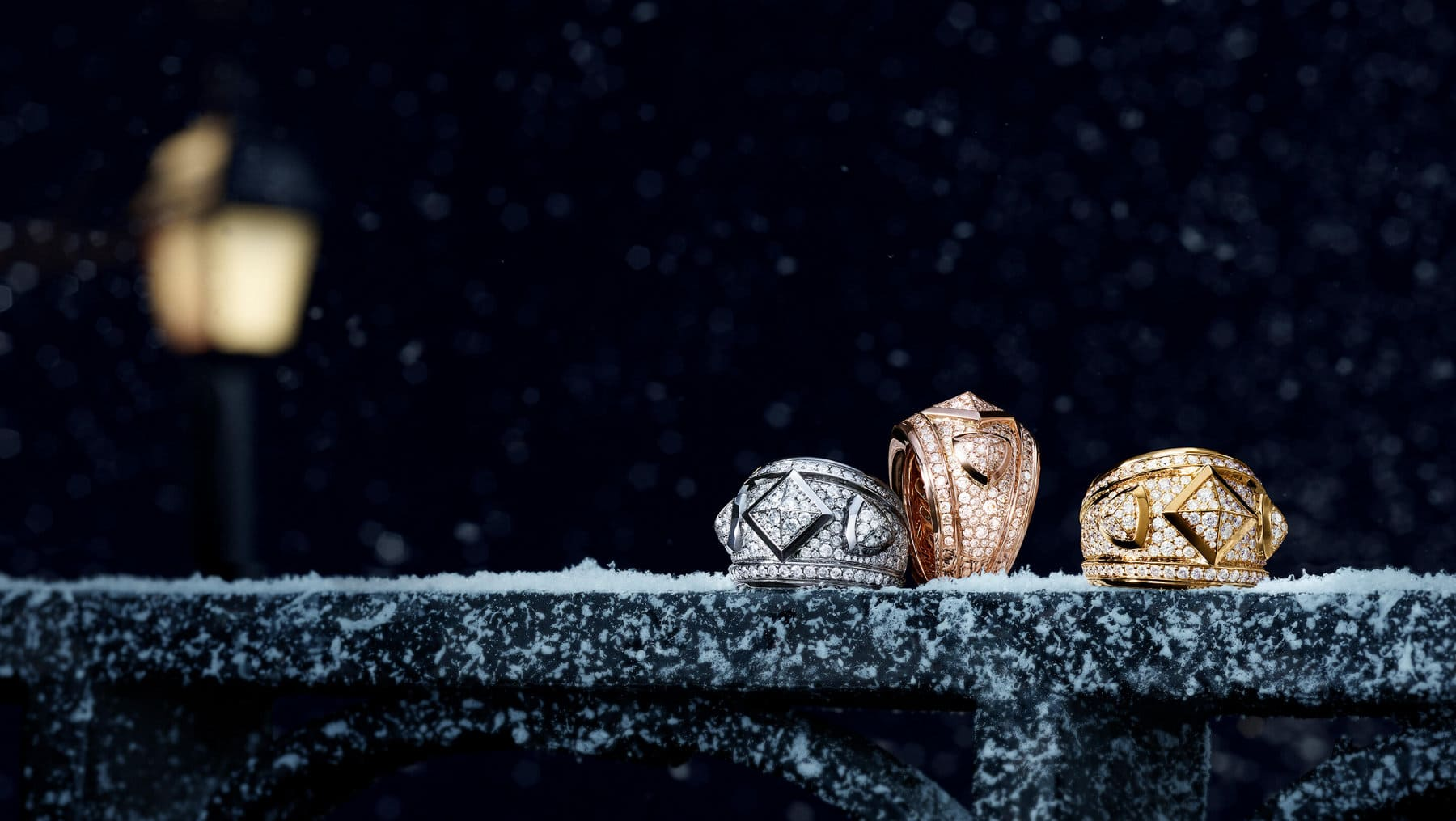 A color photograph shows three David Yurman Renaissance rings scattered atop a snow-dusted metal ledge at night. The women's jewelry is crafted from white or yellow gold with pavé white diamonds. In the dark background is the golden glow of a nearby street light.