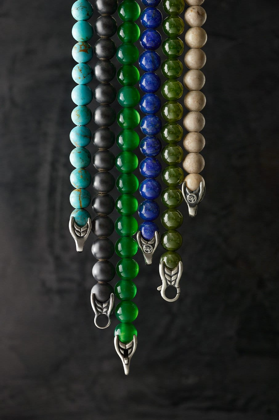 A color photo shows six David Yurman Spiritual Beads bracelets hanging in front of a black background. The jewelry is crafted from various colored gemstones and sterling silver.
