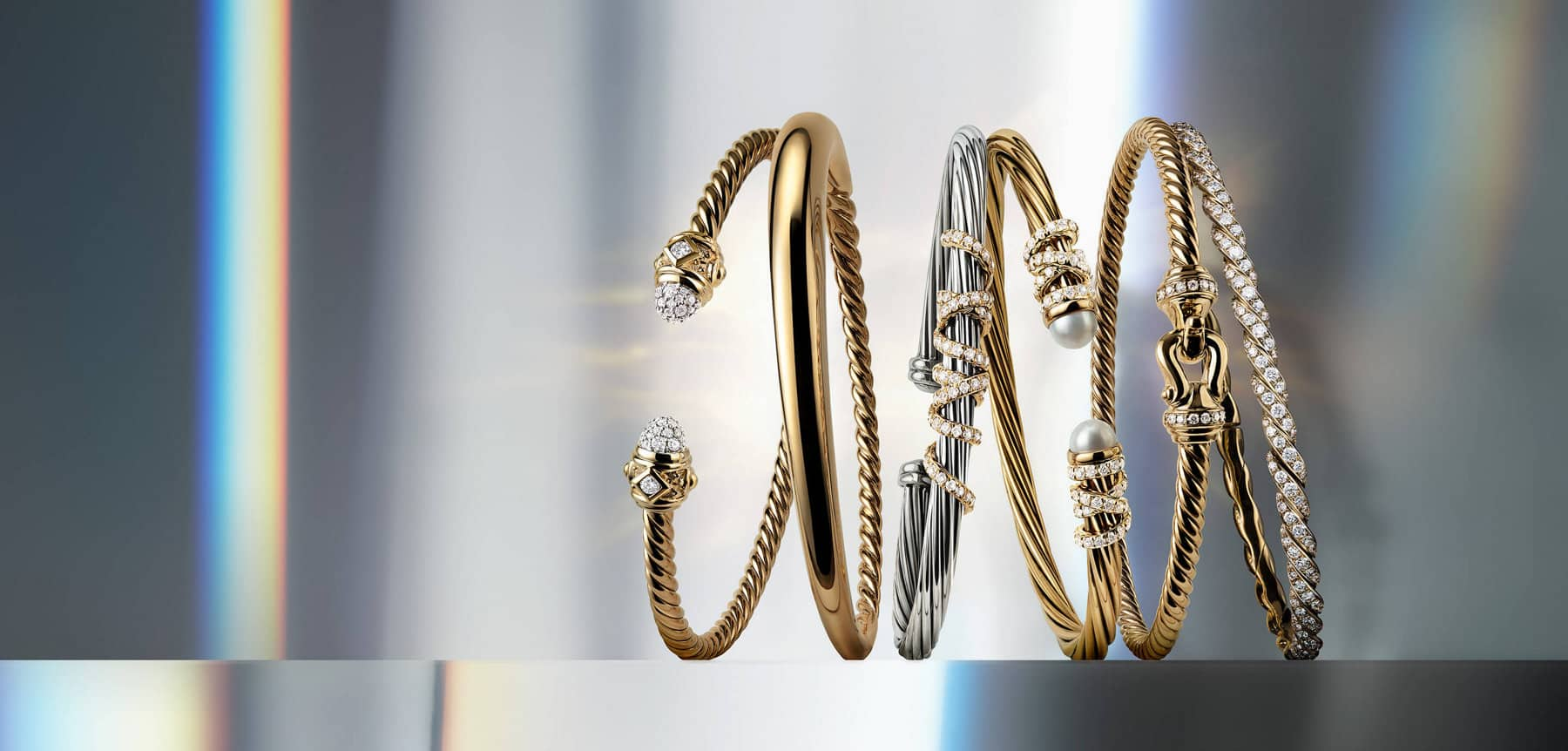 A color photo shows reflections of rainbow-hued light on a vertical stack of three David Yurman Modern Renaissance pyramid cuff bracelets in sterling silver, 18K yellow gold, and black titanium and 18K yellow gold.
