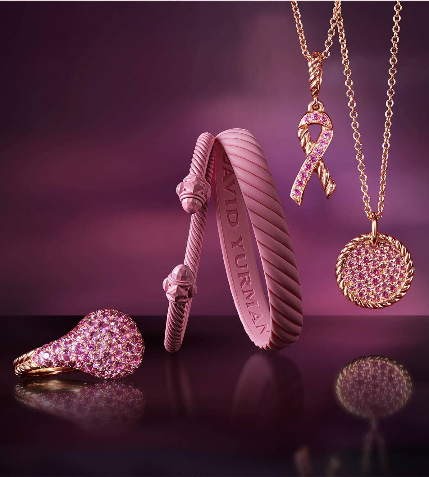 A color photograph shows a David Yurman pinky ring sitting on a black reflective surface to the left of an aluminum Renaissance bracelet, Cable bracelet and two David Yurman necklaces hanging in front of a dark backdrop with pink reflections of light. The women's jewelry is crafted from pink-colored aluminum, rubber or 18K rose gold with pavé pink sapphires. The necklaces are strung with ribbon- and circle-shaped charms.