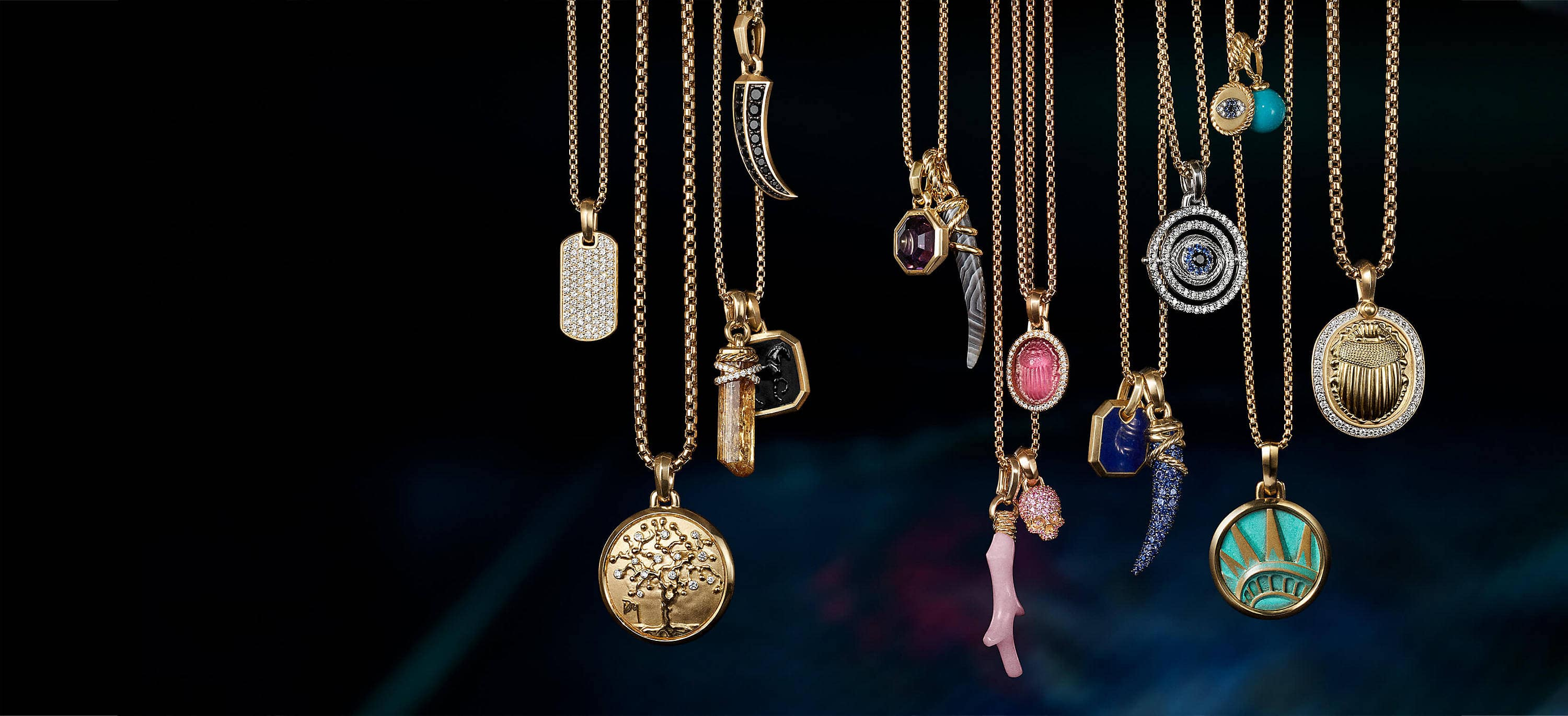 A color photograph shows 15 David Yurman amulet pendants hanging from a horizontal row of chain necklaces in front of an illuminated colorful backdrop. The women's jewelry is crafted from 18K yellow gold with or without pavé diamonds and an array of colored gemstones. The pendants come in various shapes such as a dog tag, branch of coral, horn, dagger, or skull or depict a multitude of images such as a tree of life and a scarab.